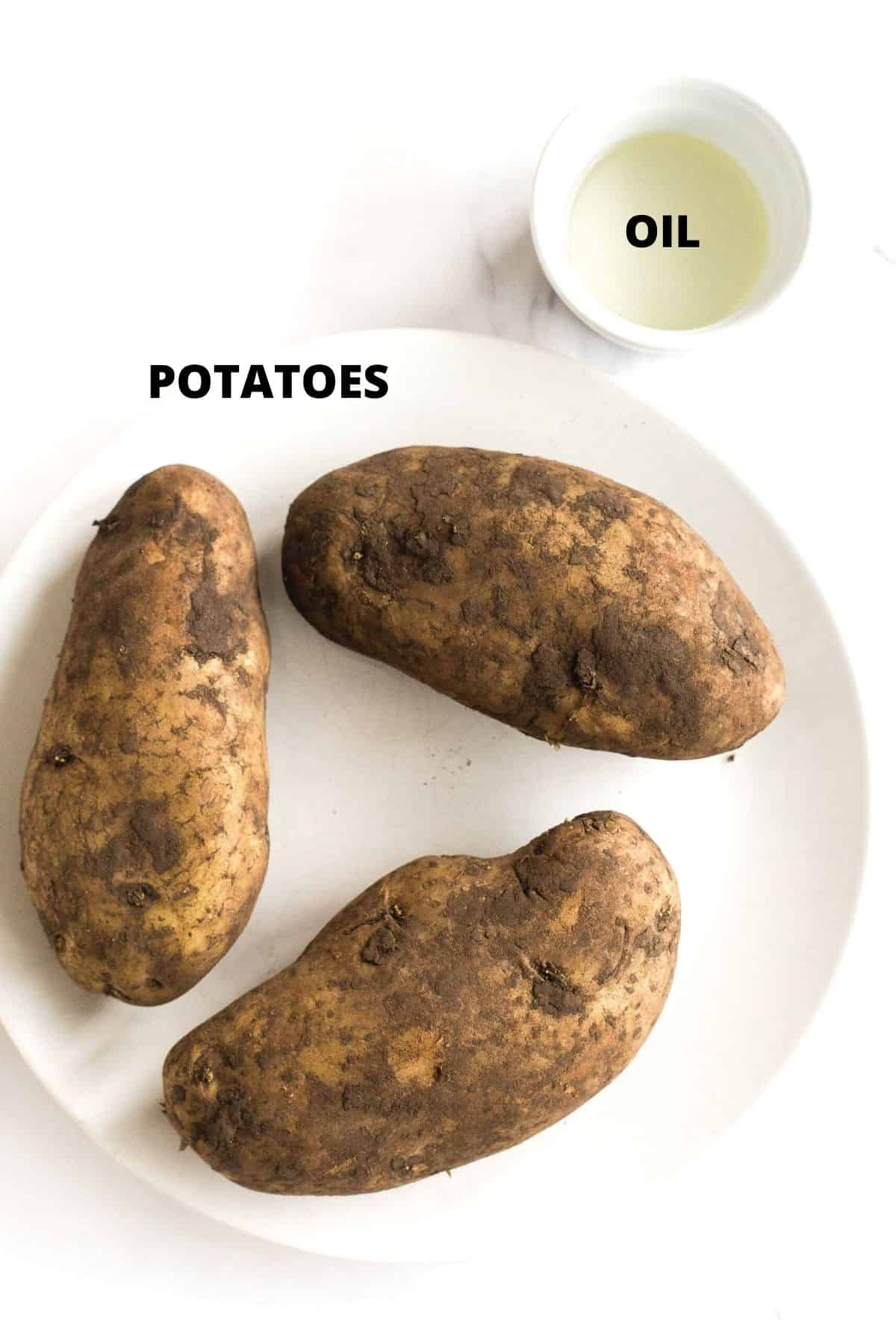 Russet potatoes on a plate and a small bowl of oil next to it.