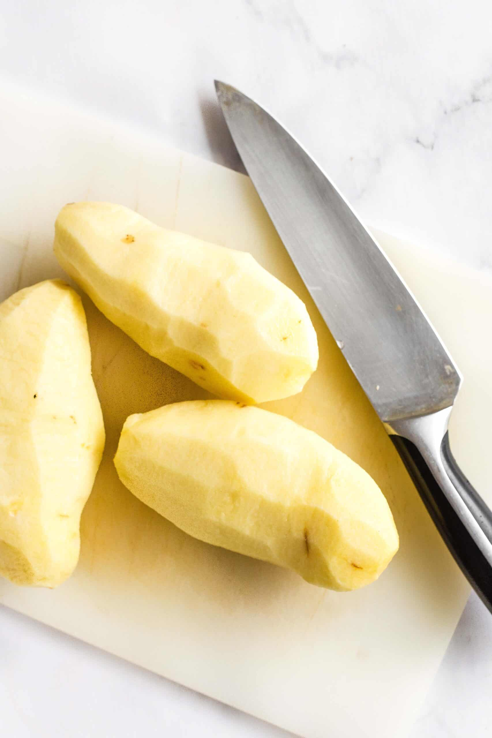Peeled potatoes and a knife on a chopping board.