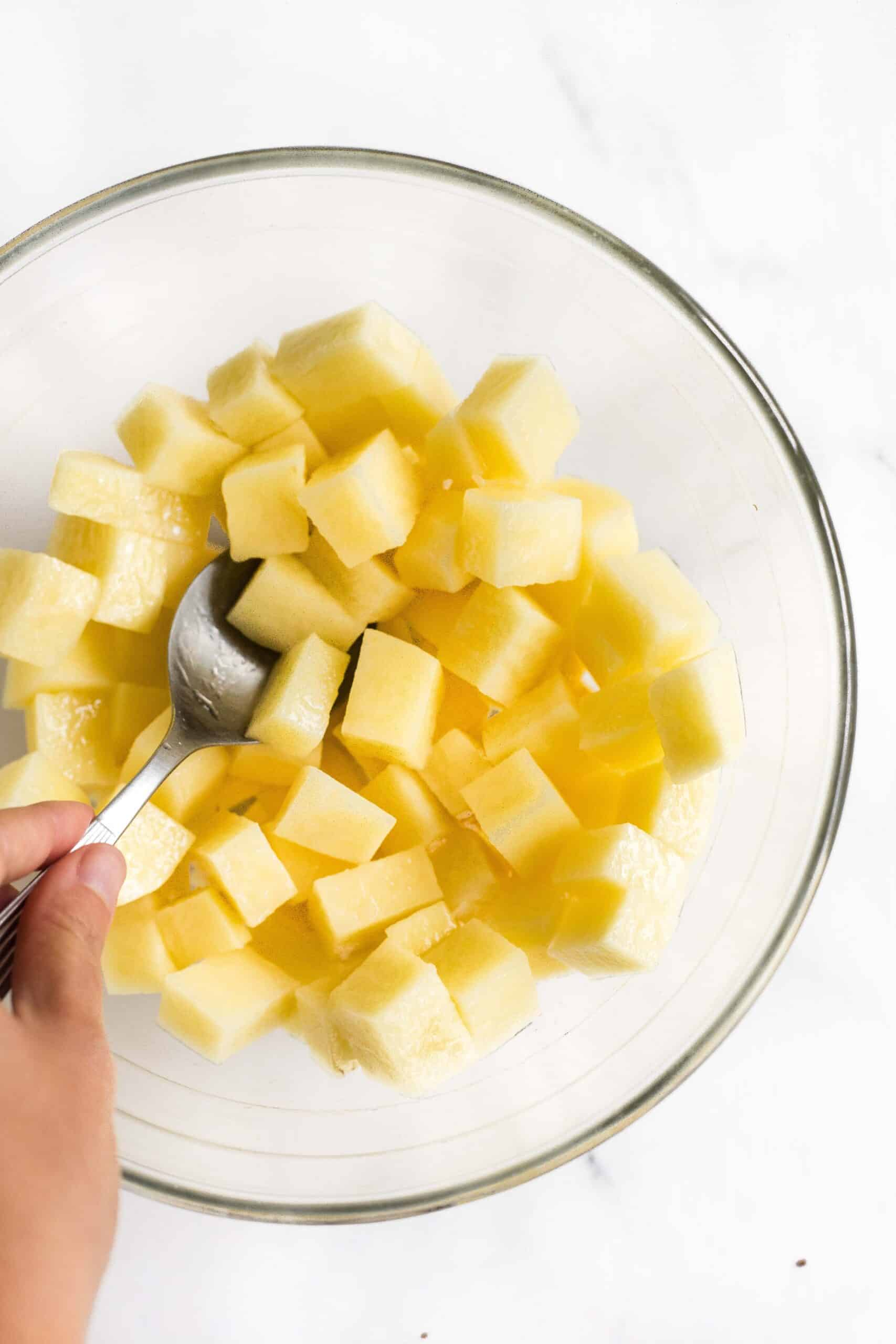 Mixing diced potatoes with oil in a large glass bowl.