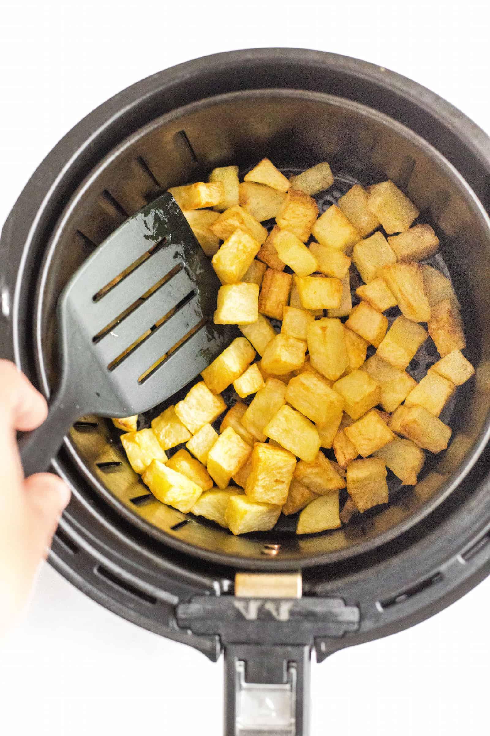 Tossing air fryer diced potatoes in an air fryer basket.