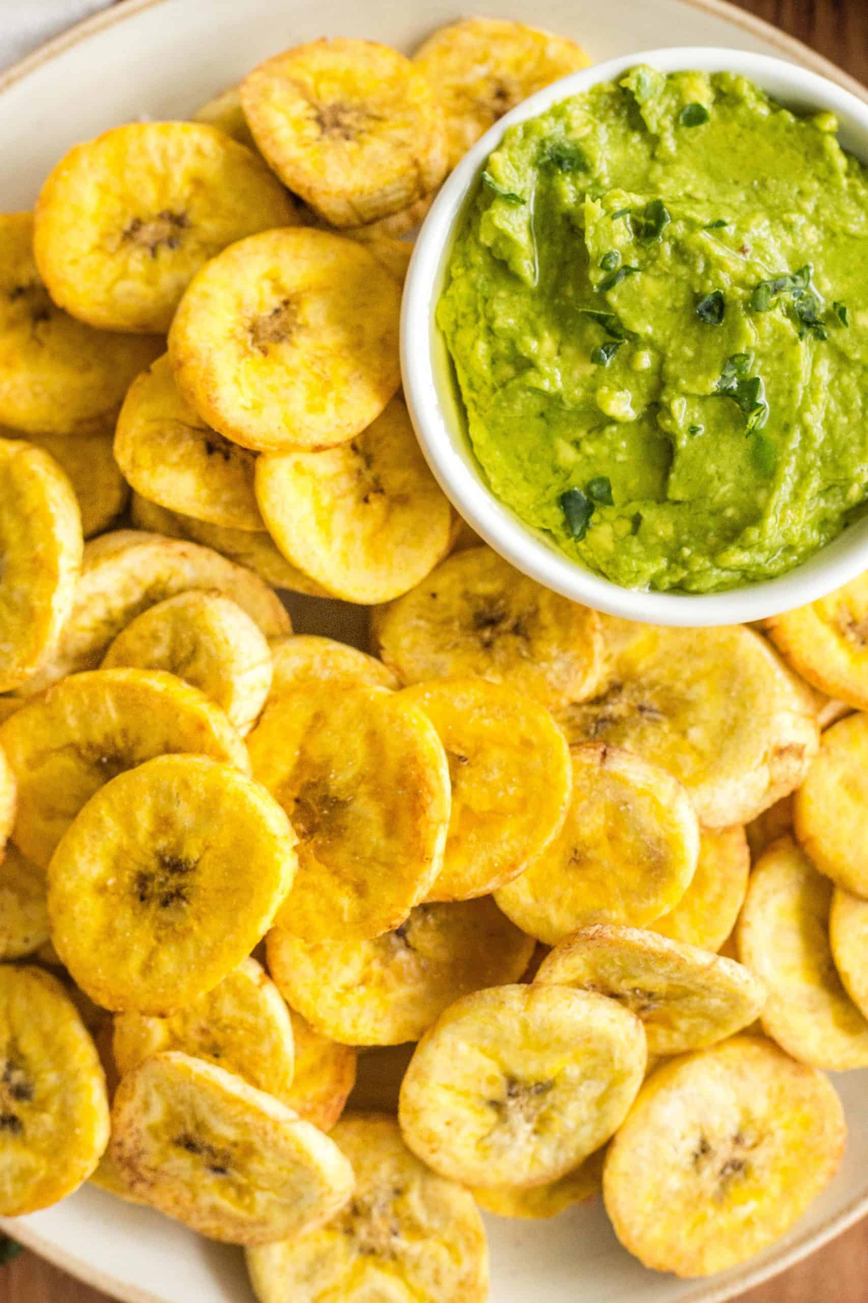 Close up shot of air fryer plantains and a bowl of guacamole.