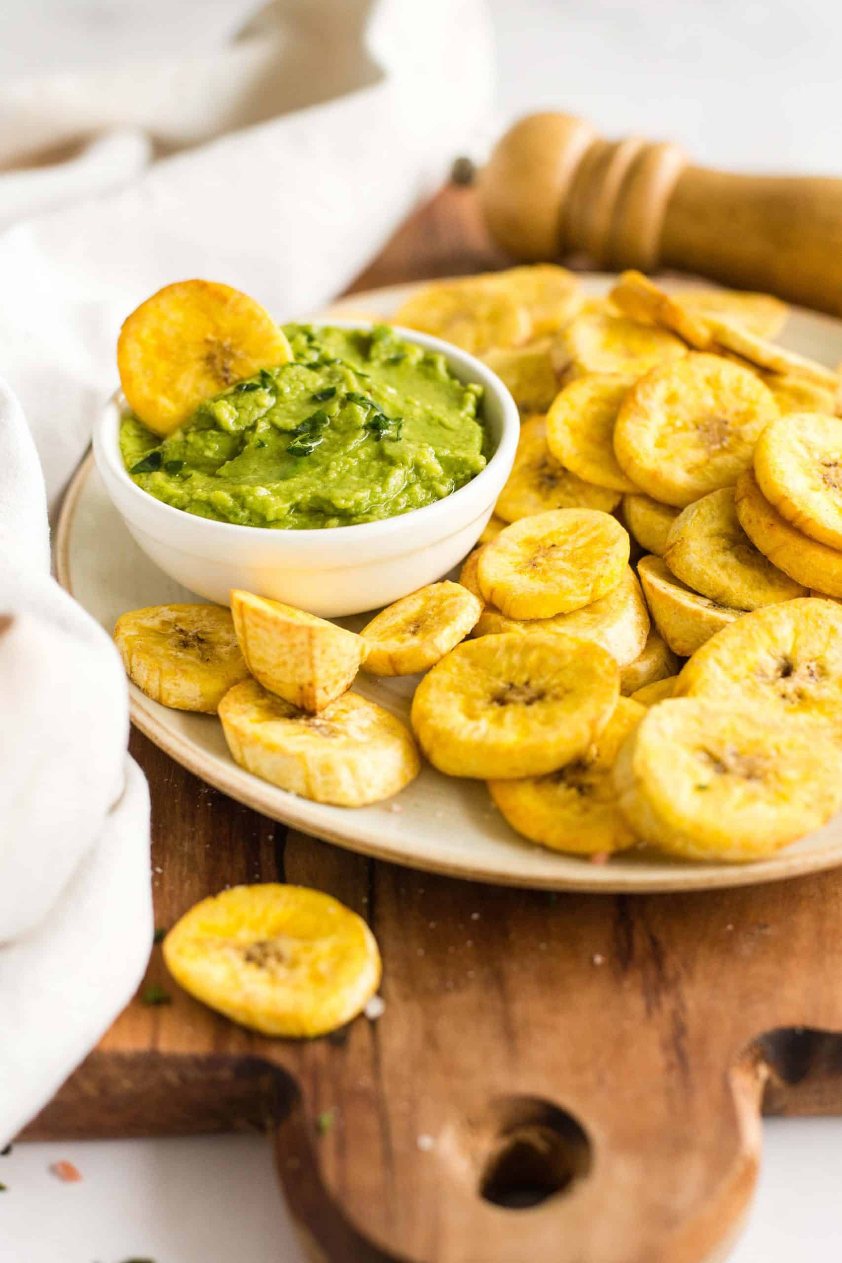 A plantain chip in a small bowl of guacamole alongside a plate of plantains.