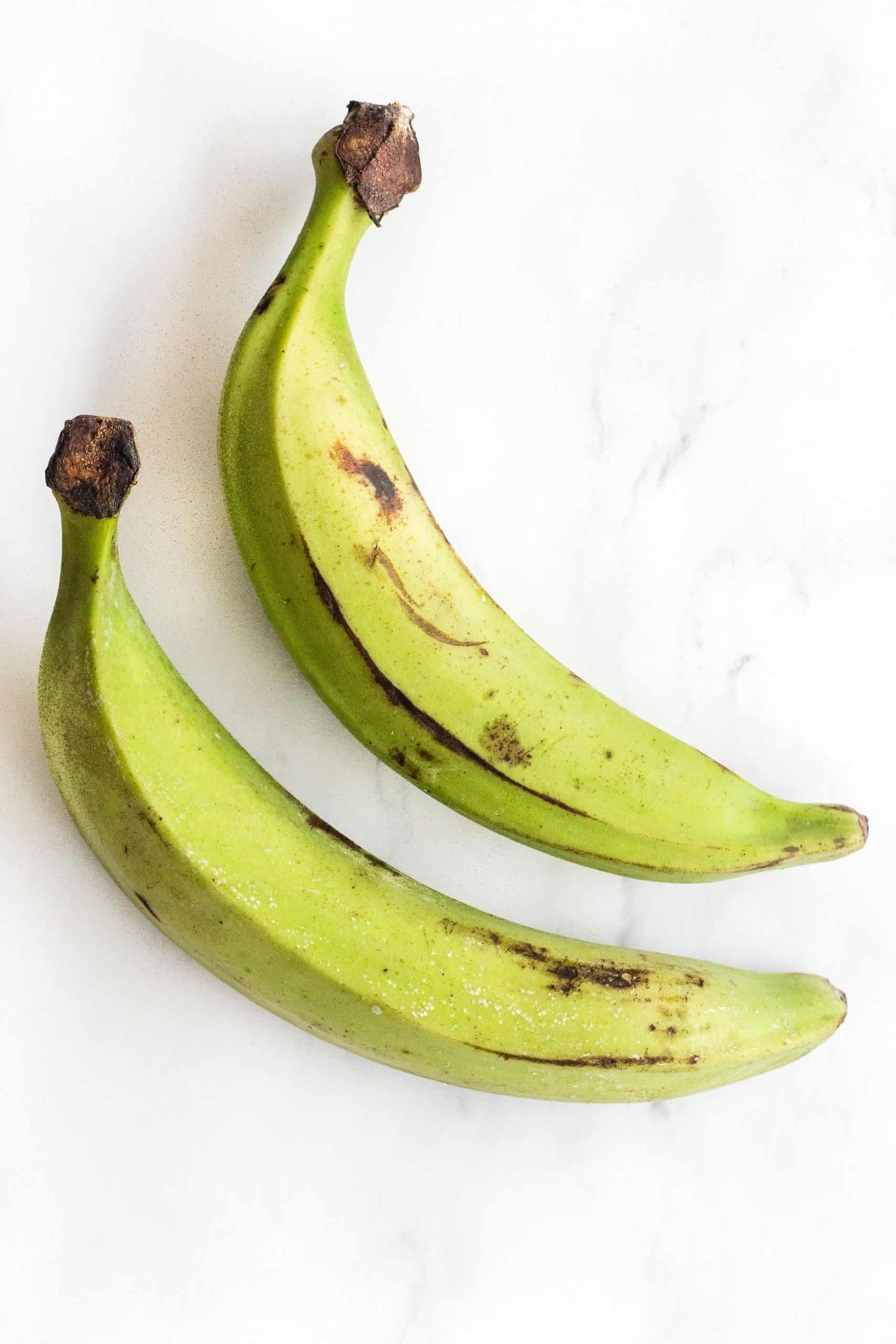 Green unripe plantains on a marble board.