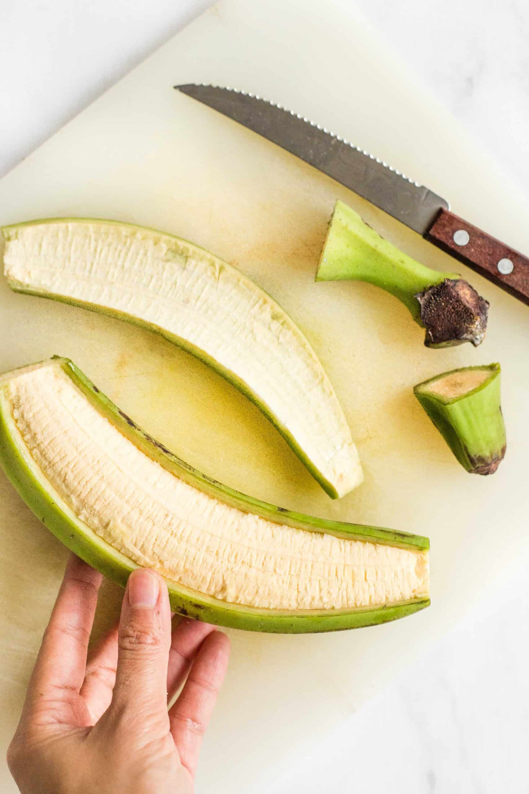 Holding a half-peeled green plantain.