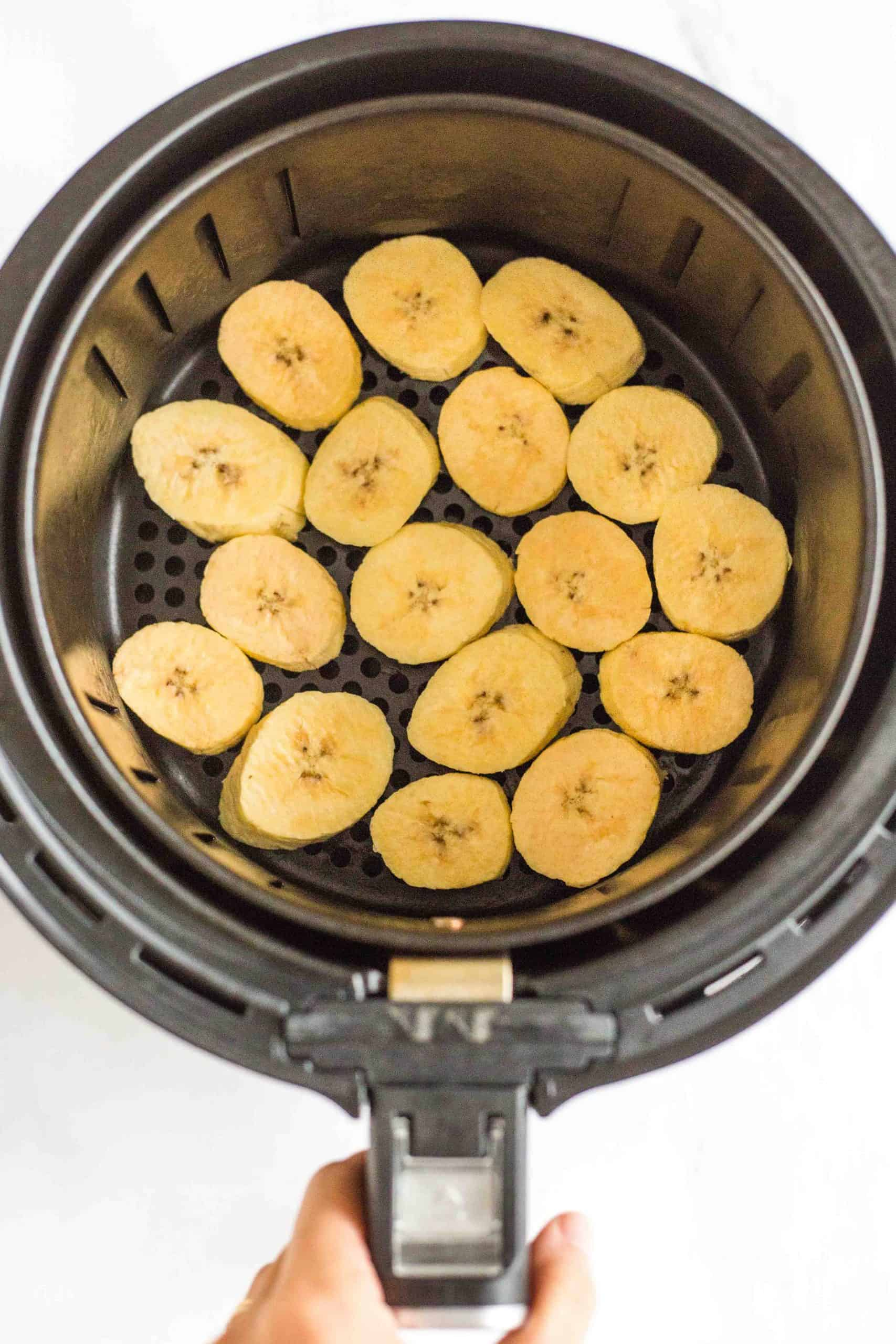 Sliced plantains in a single layer in air fryer basket.