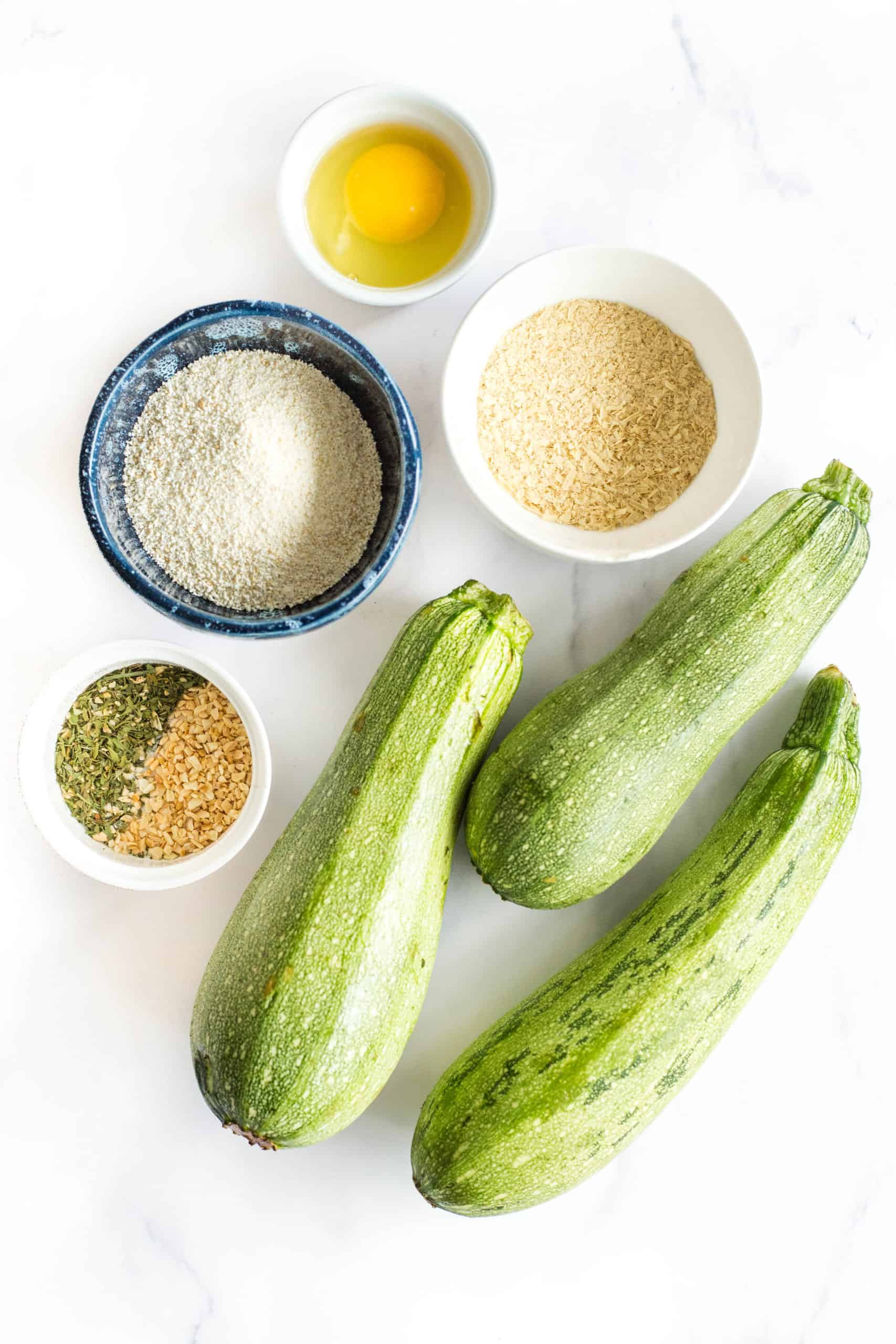 Ingredients for making zucchini fries placed on a marble board - fresh zucchini, breadcrumbs, nutritional yeast, granulated garlic, dried parsley, and an egg.