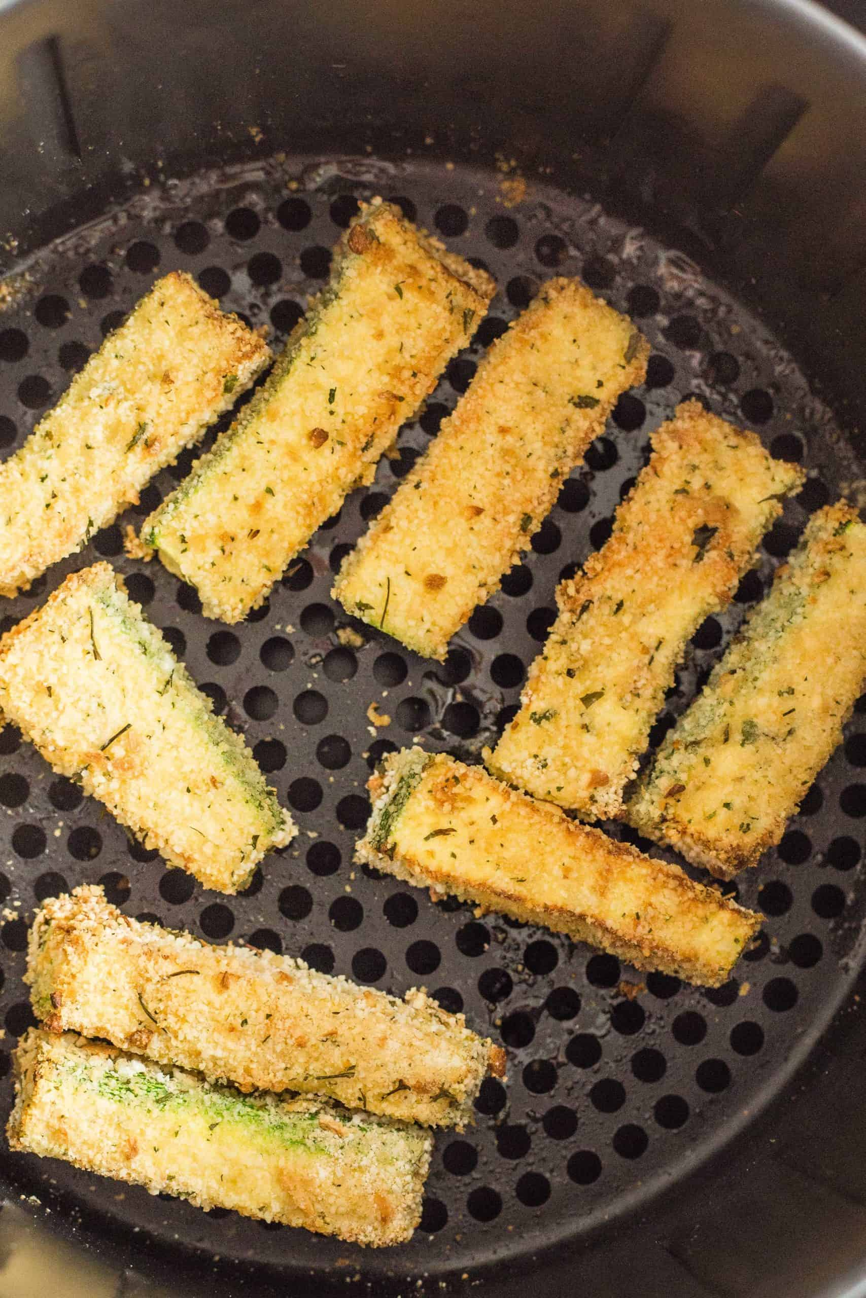 Freshly cooked zucchini fries in an air fryer basket.
