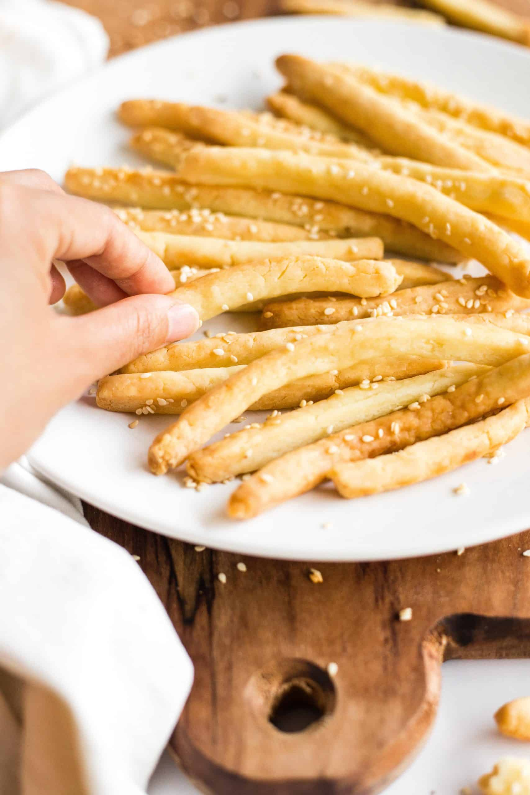 Hand reaching for a breadstick on a plate full of gluten-free breadsticks.