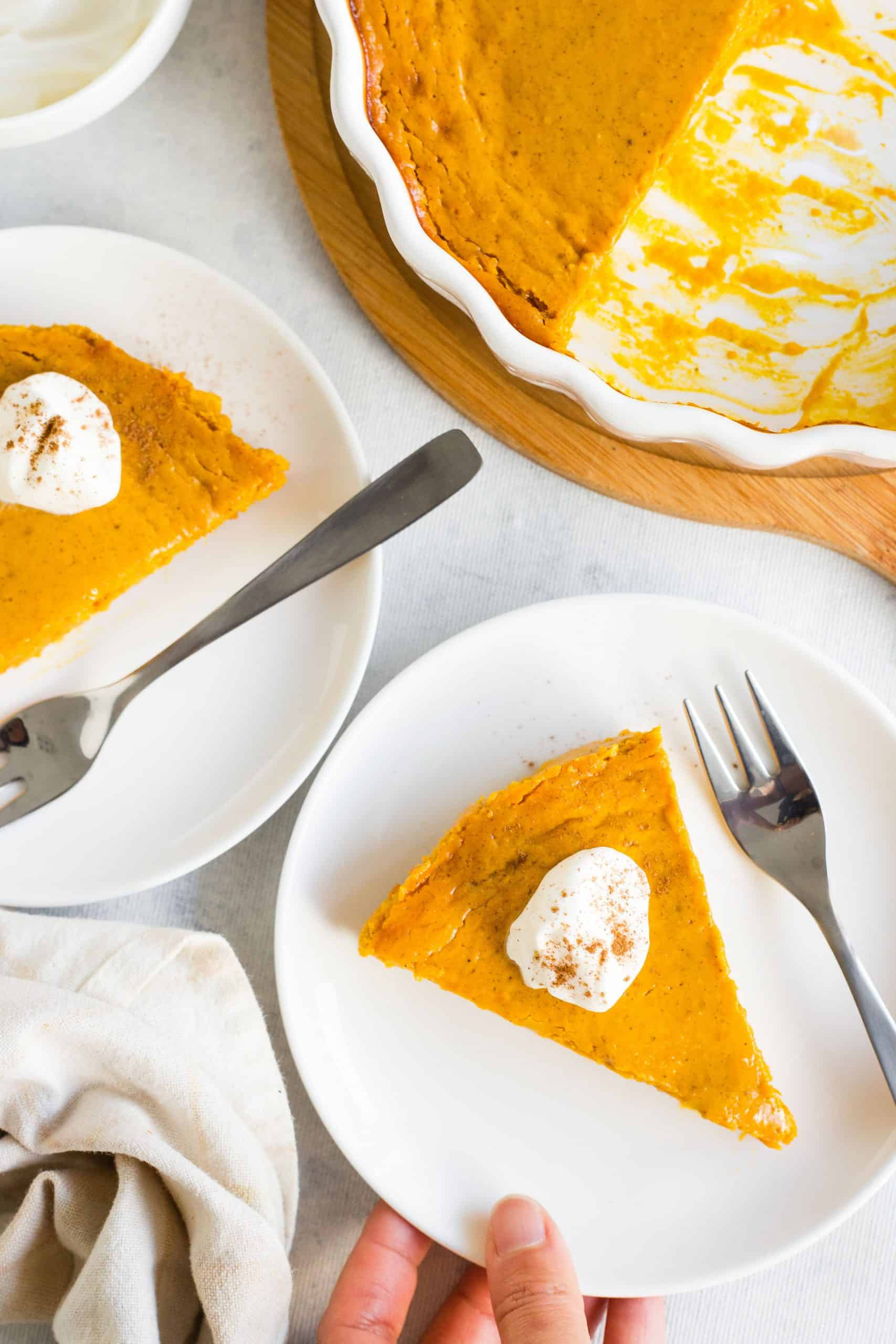 Plates of sliced pumpkin pie on a table.