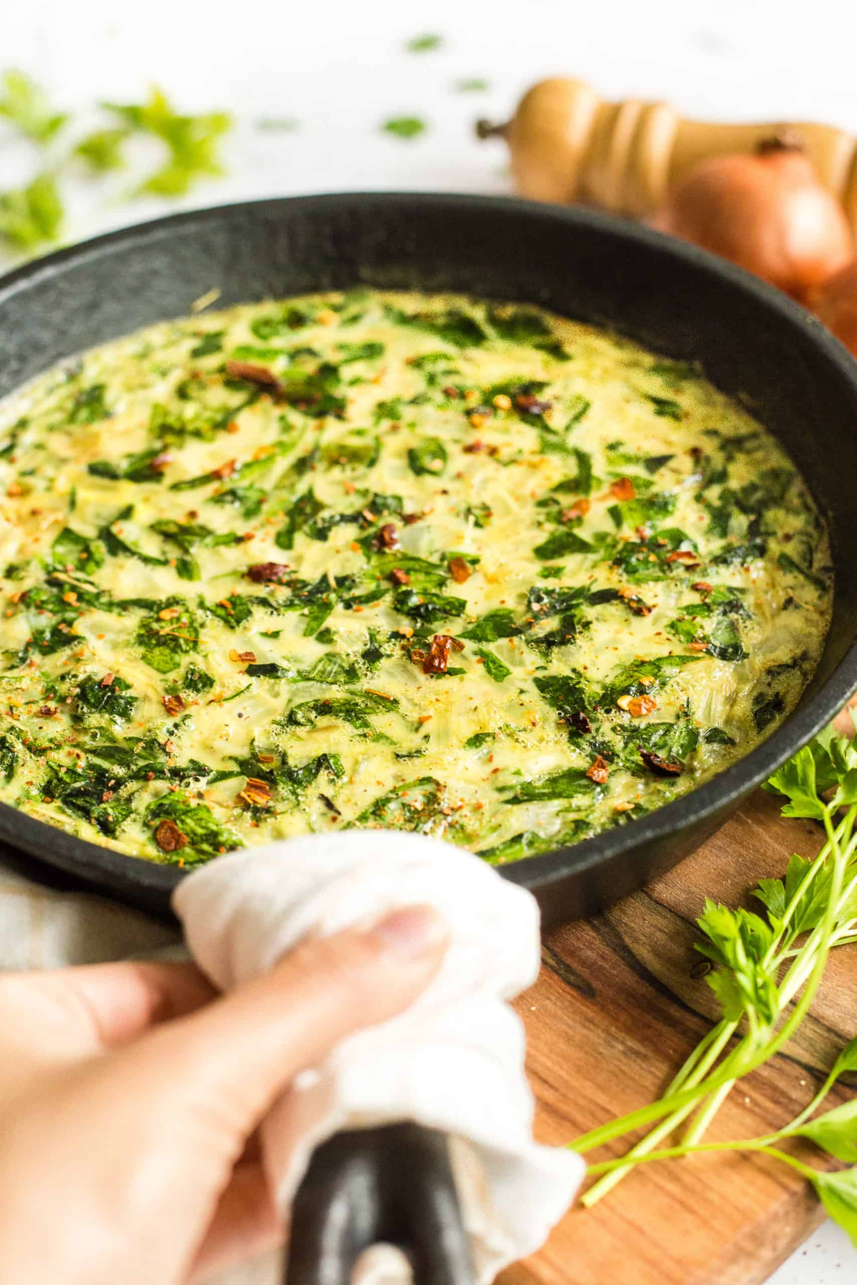 Hand holding a cast iron skillet with crustless spinach quiche.