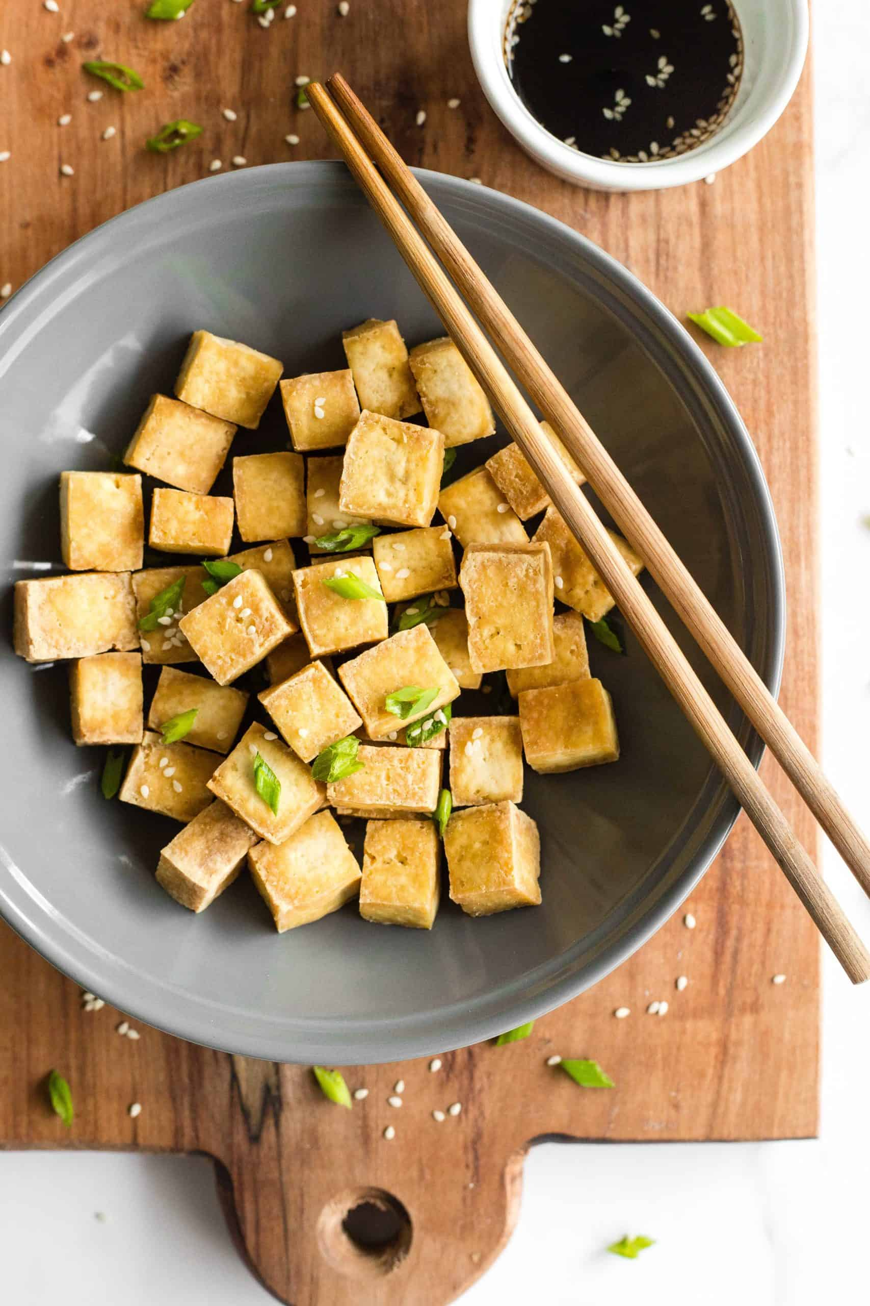 A bowl of crispy air fryer tofu cubes and chopsticks on a wooden board alongside a serving of soy sauce.
