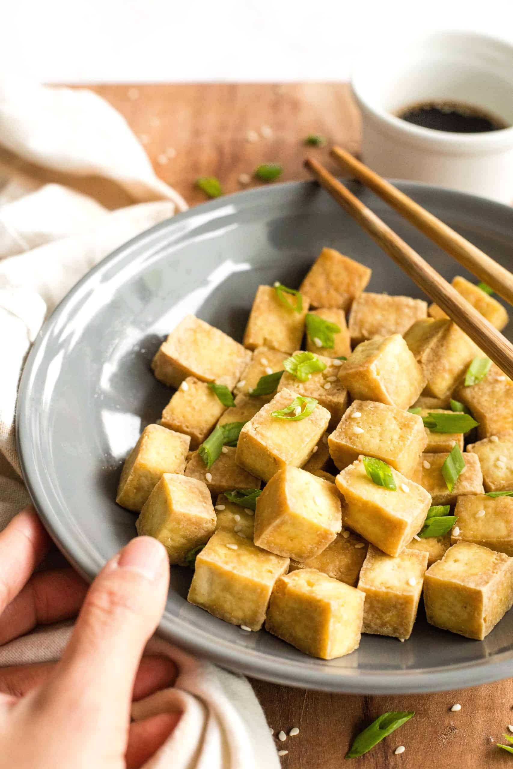 Hand holding a grey bowl of crispy air fryer tofu cubes.