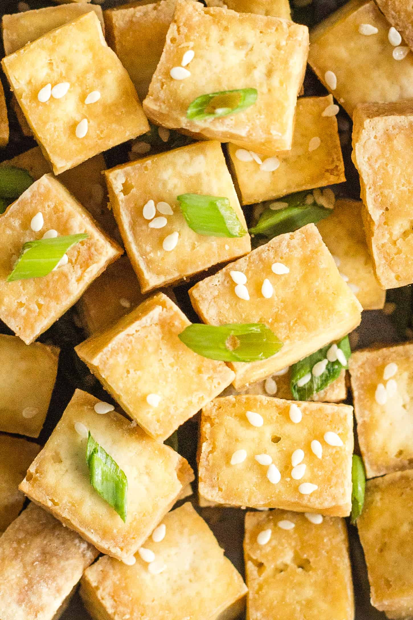 Up close shot of crispy air fryer tofu sprinkled with sesame seeds and chopped spring onions.
