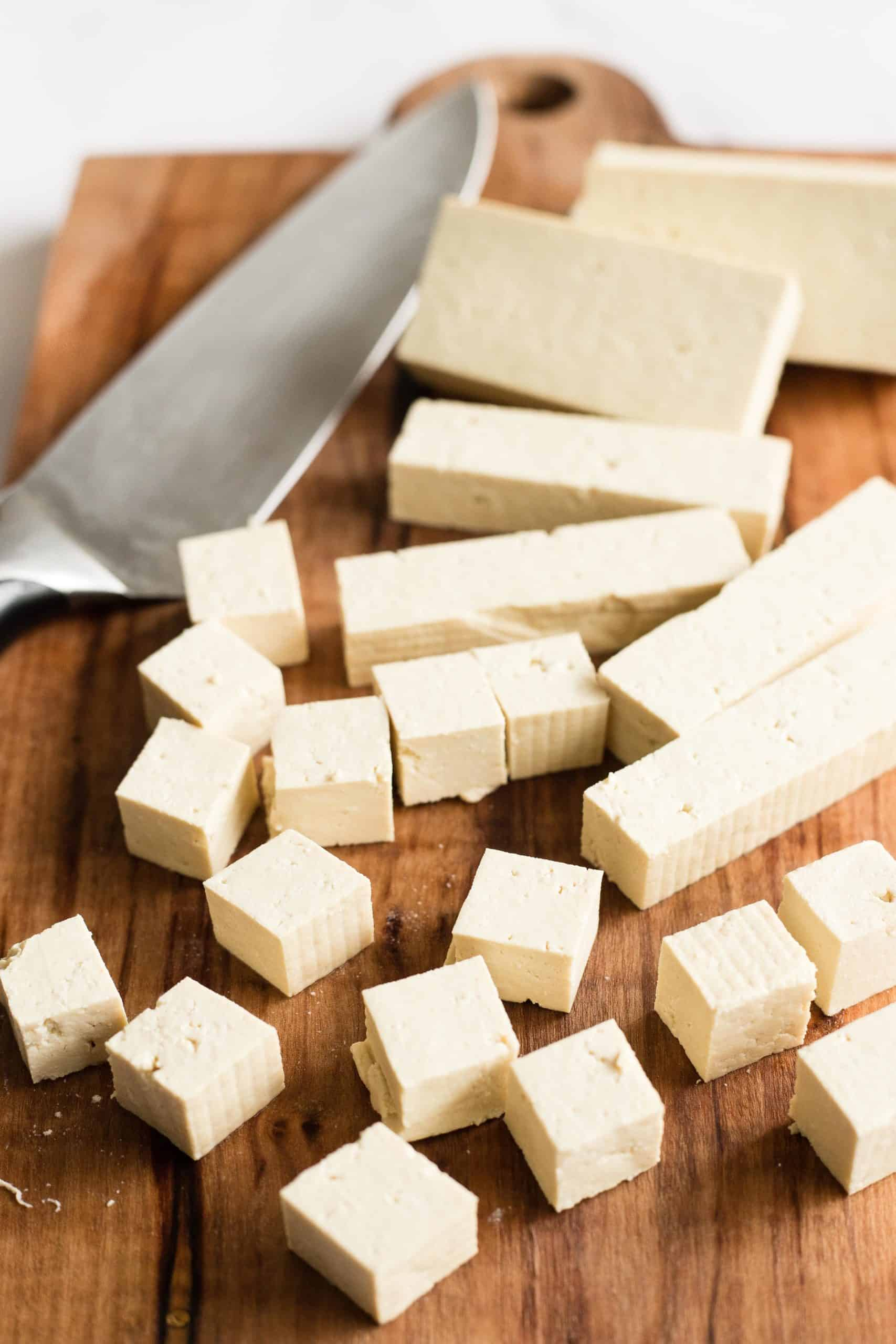 Tofu being cut into small cubes on a wooden chopping board.