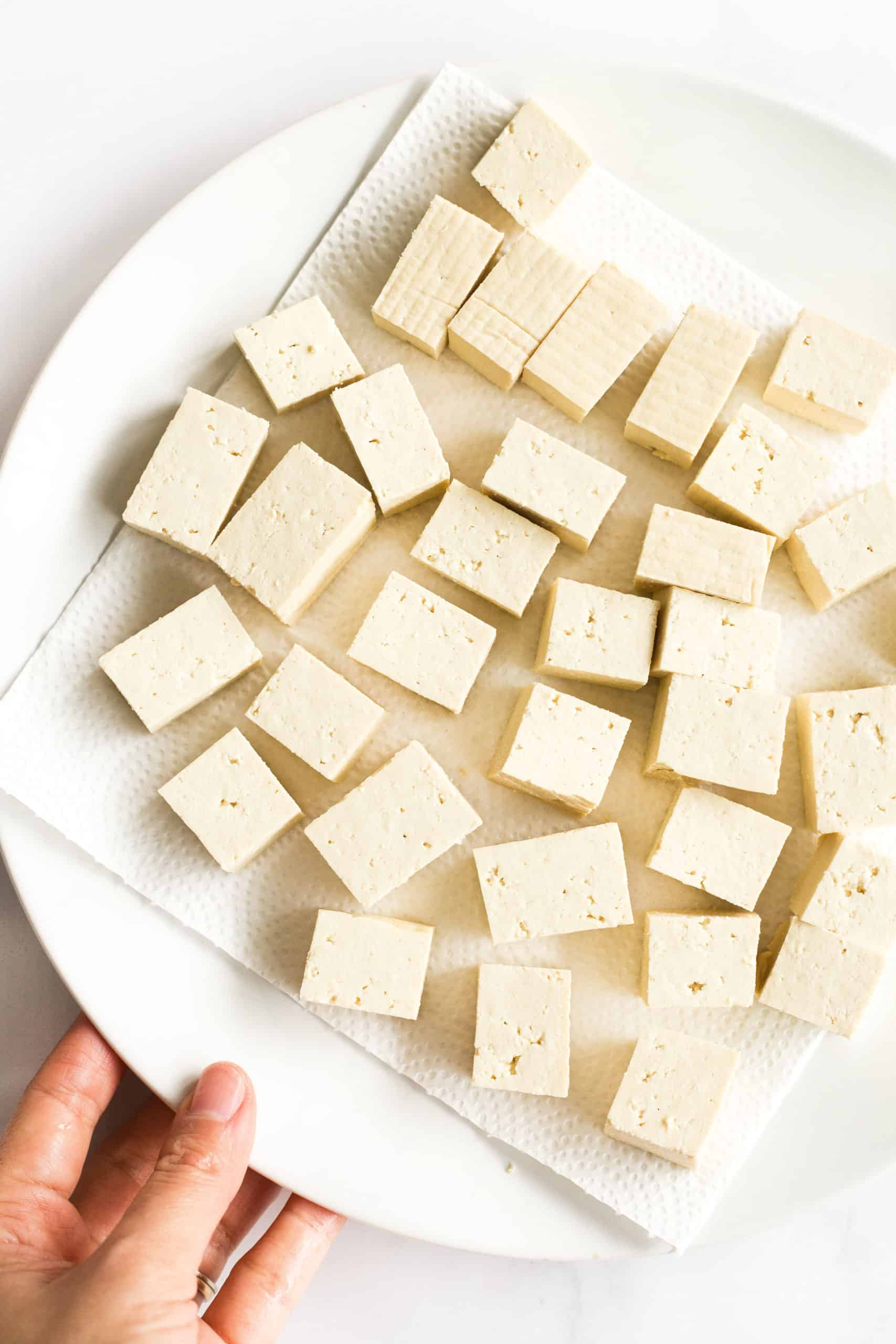 Tofu cubes on a paper towel-lined plate ready to be pressed.