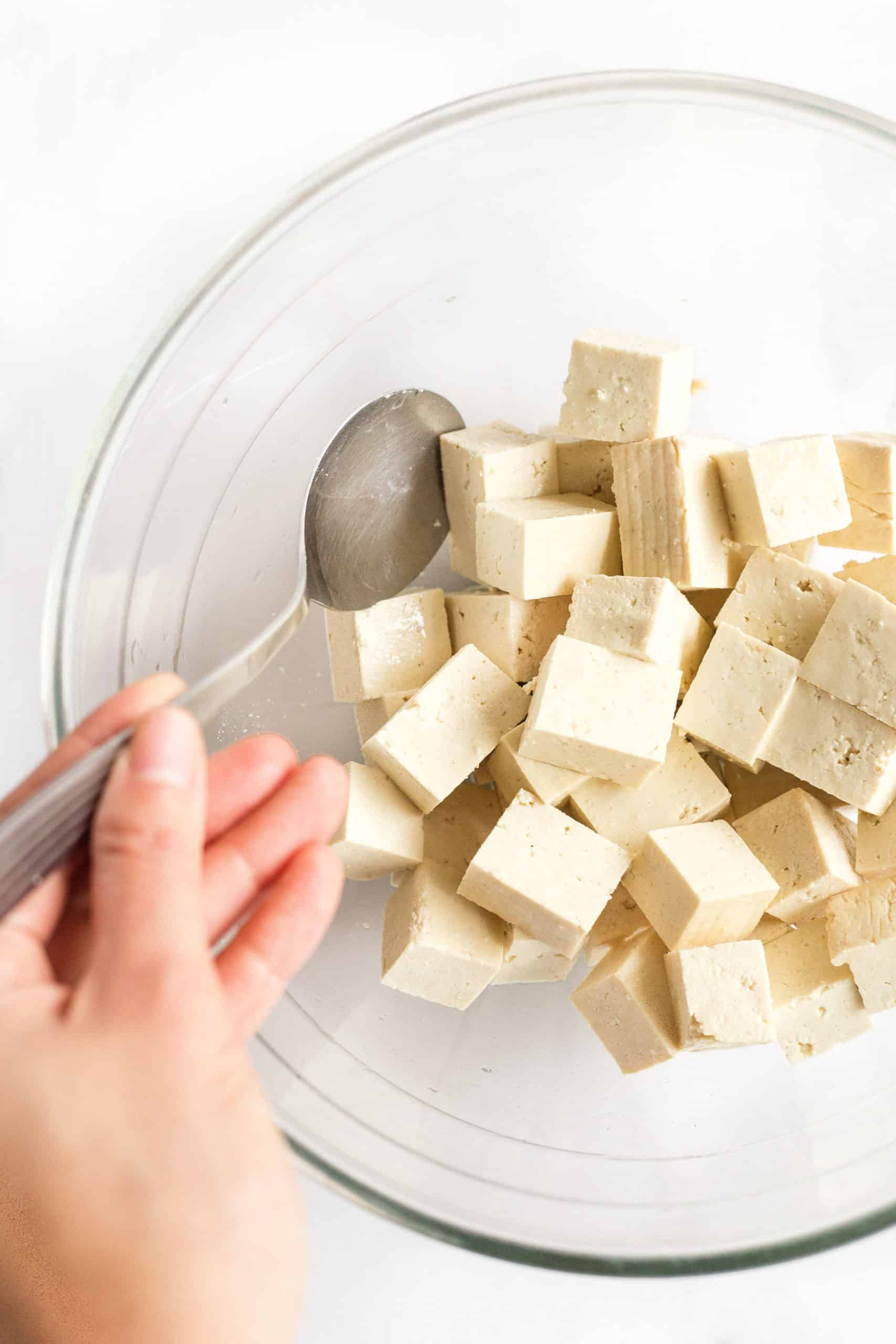 Hand using a spoon to toss cubed tofu with oil in a glass mixing bowl.