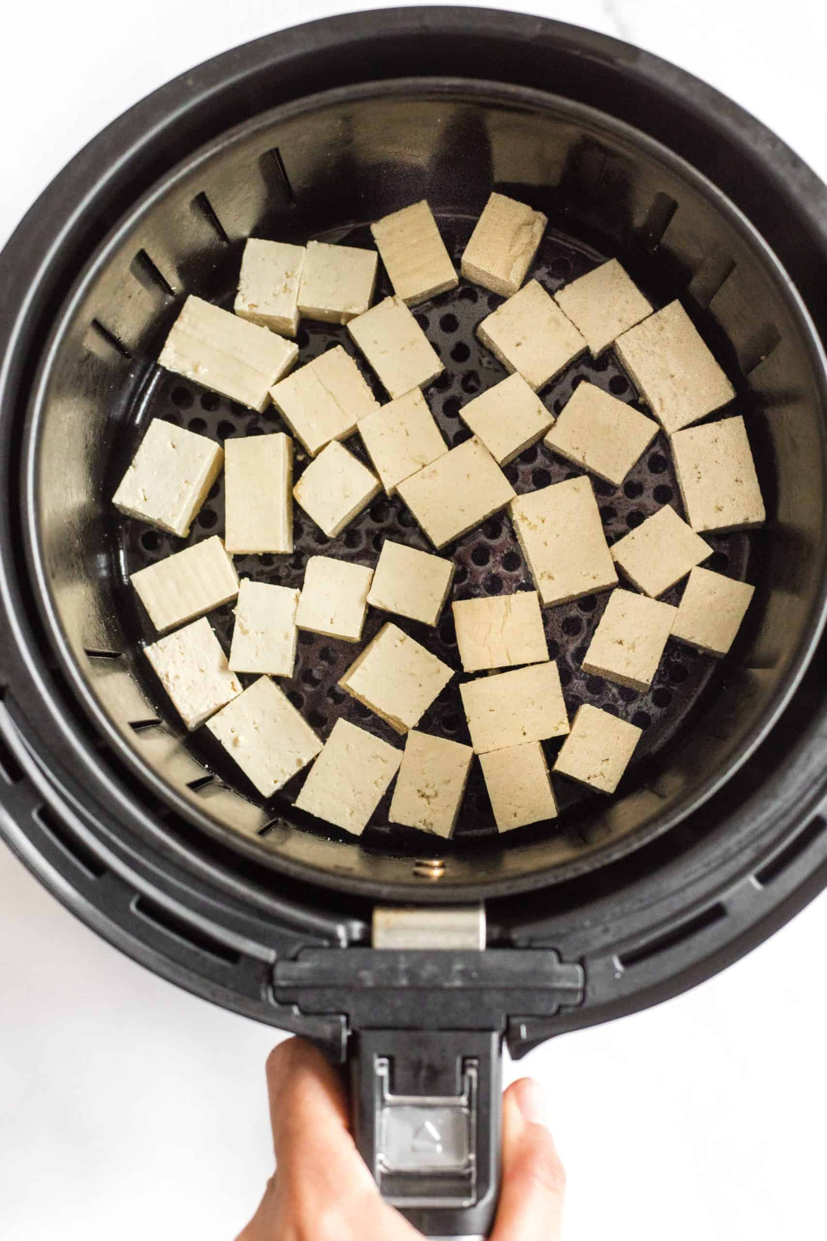 Tofu cubes in a single layer in the air fryer basket ready to be cooked.