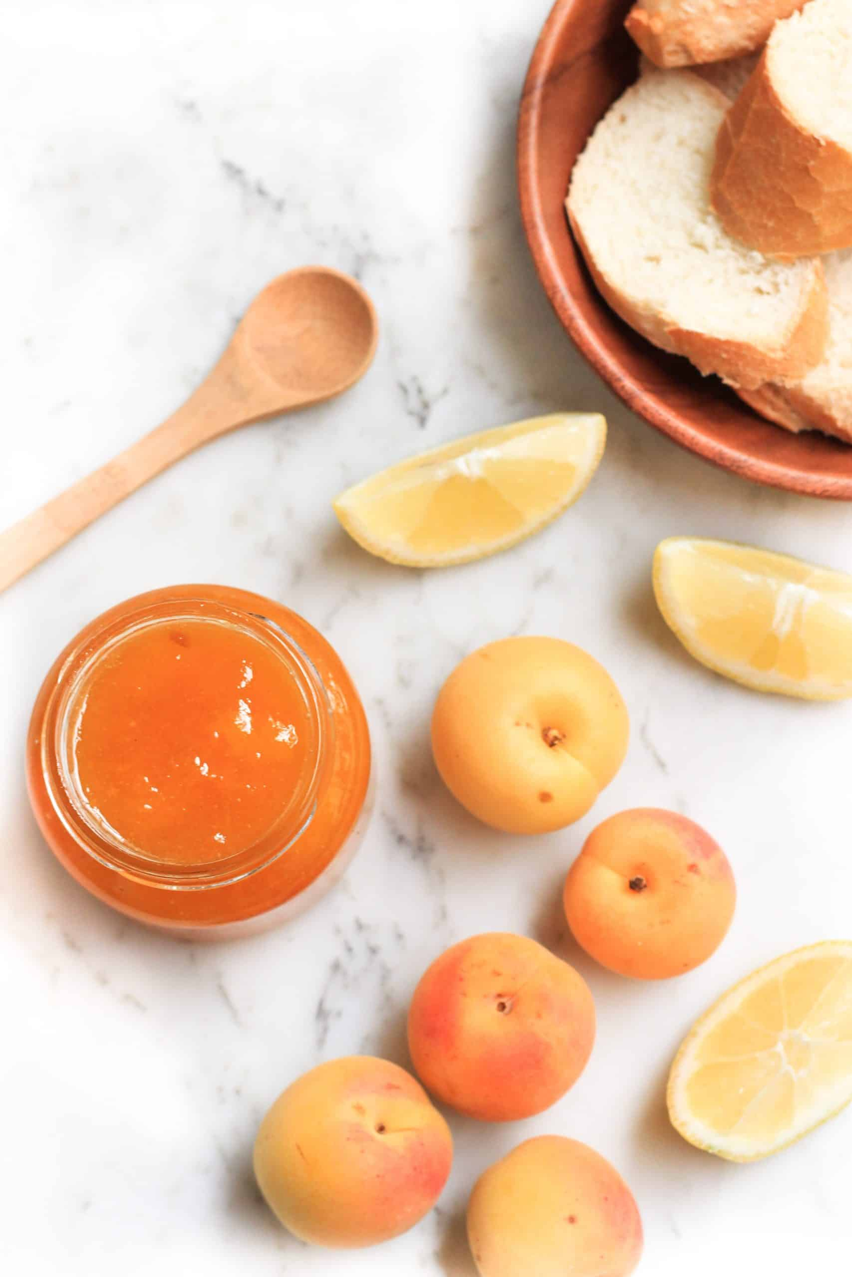 An open jar of jam, apricots, lemons, and bread on a marble board.