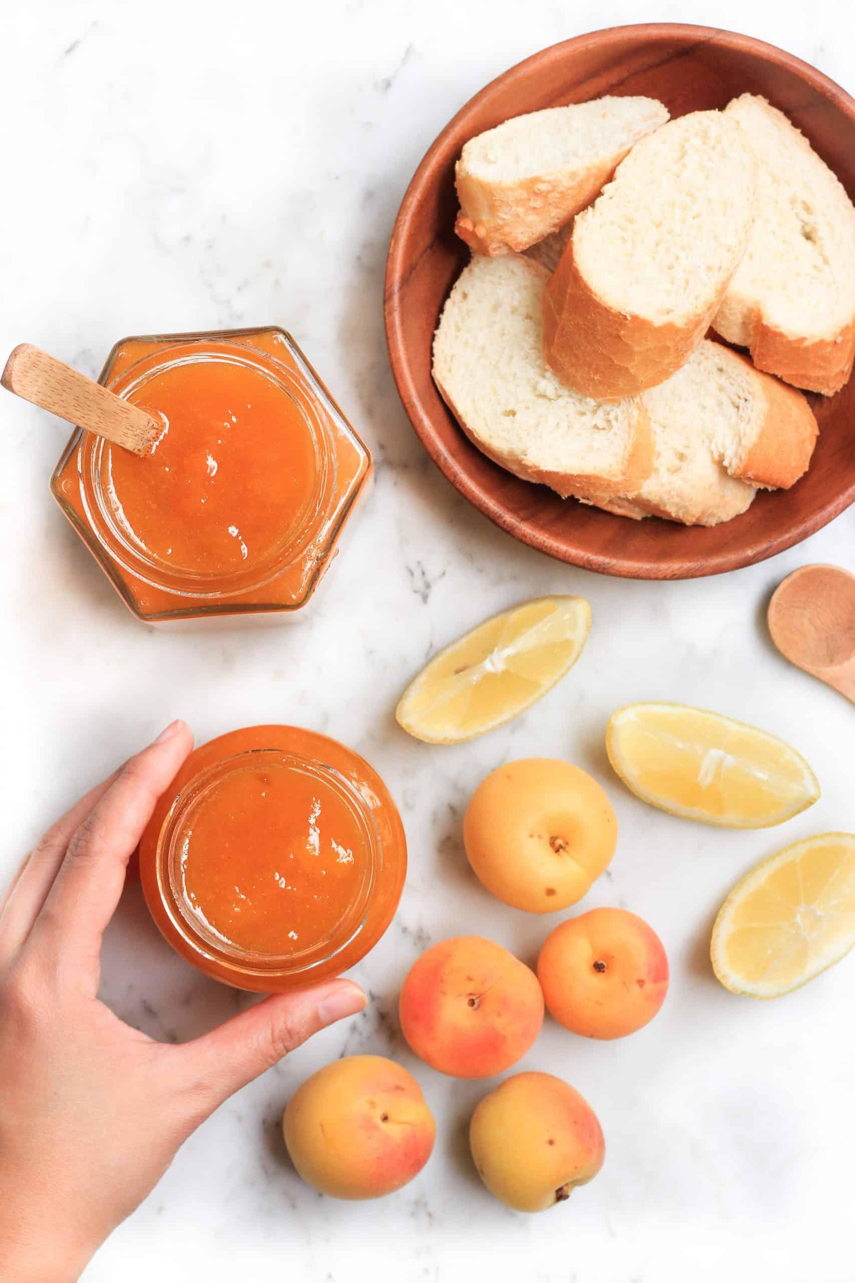 Hand reaching for fresh apricot jam.
