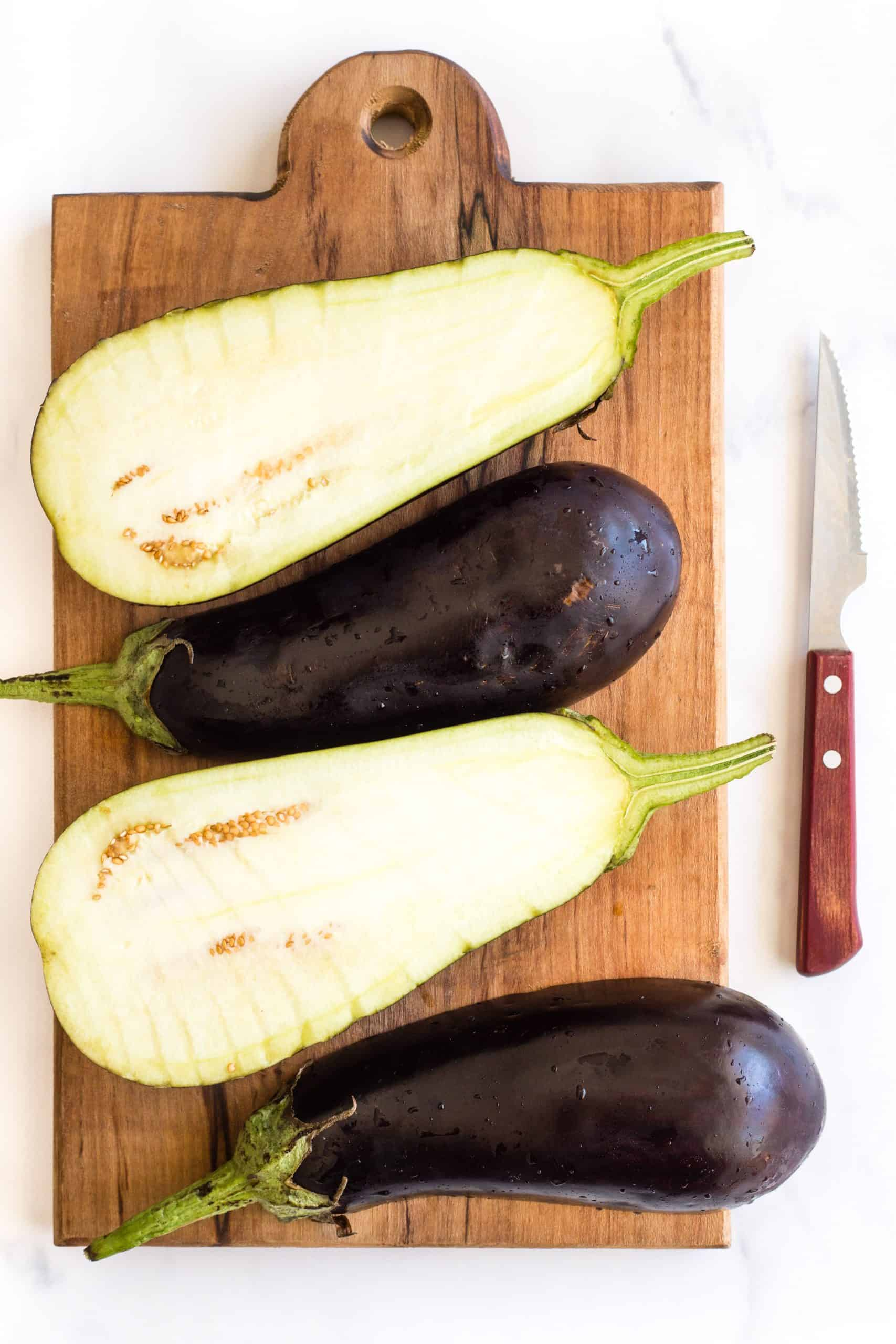 Eggplant halves on a wooden board.