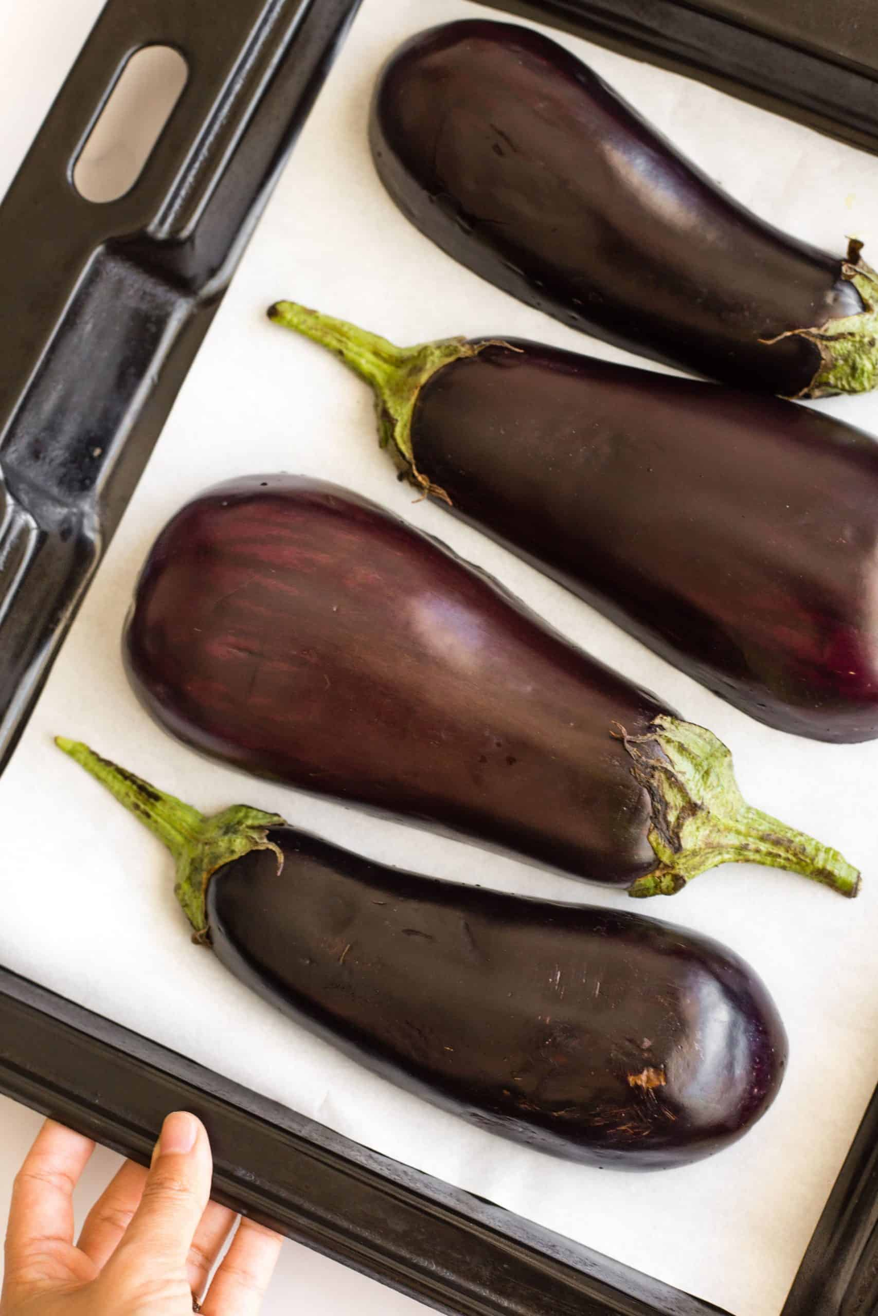 Eggplant halves on a parchment-lined baking sheet.