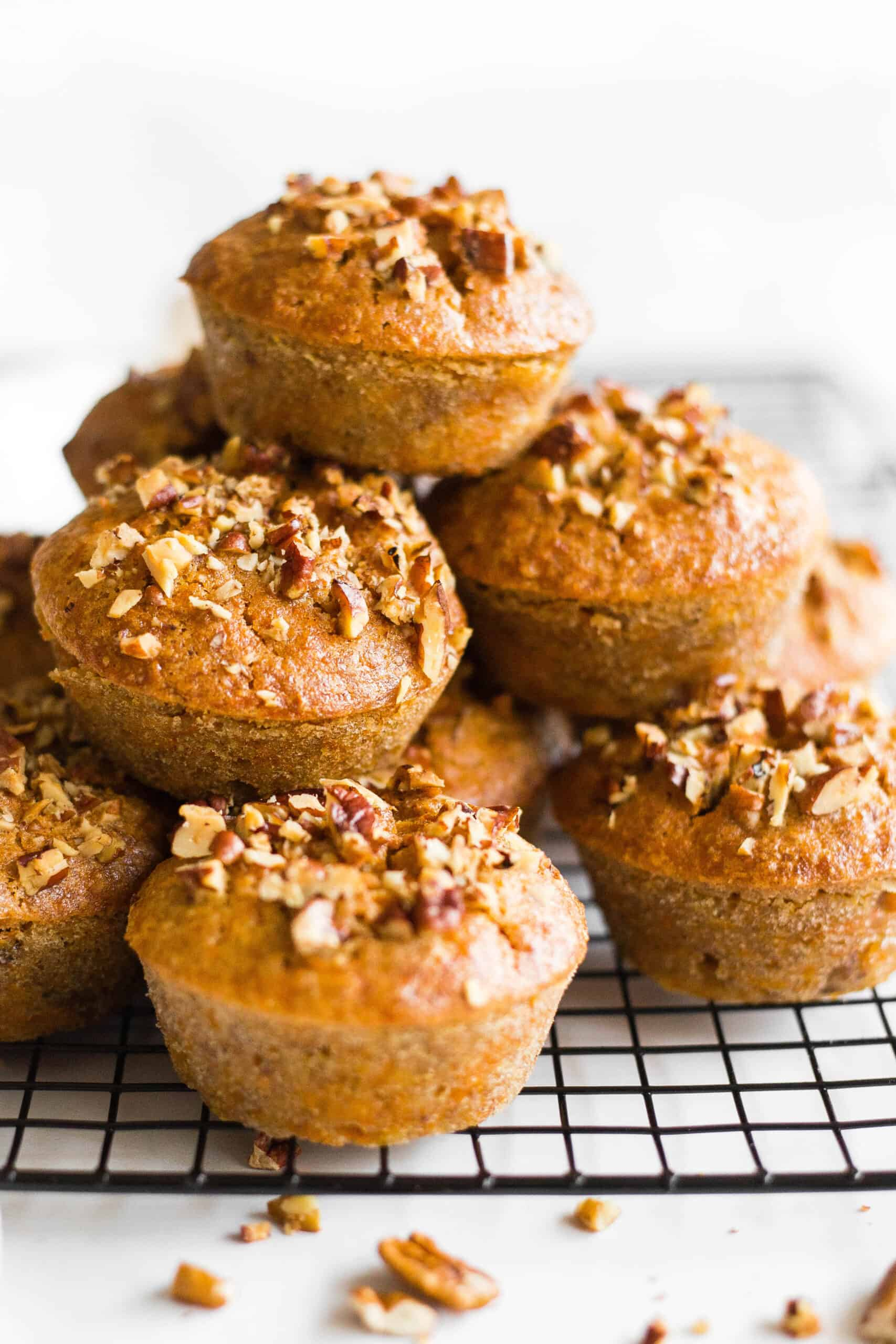 A stack of gluten-free carrot muffins on a cooling rack.