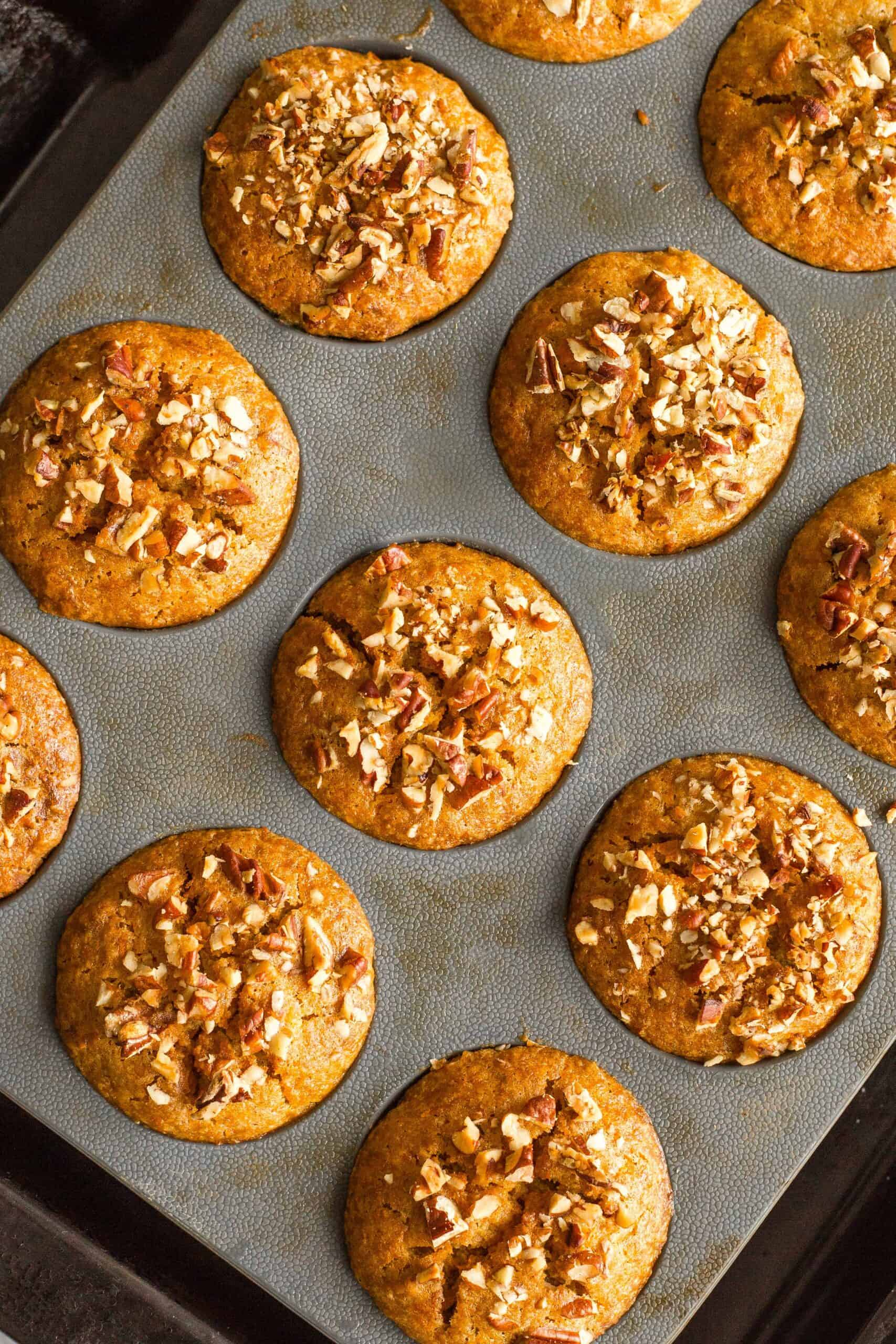 Freshly baked carrot muffins in a muffin pan.