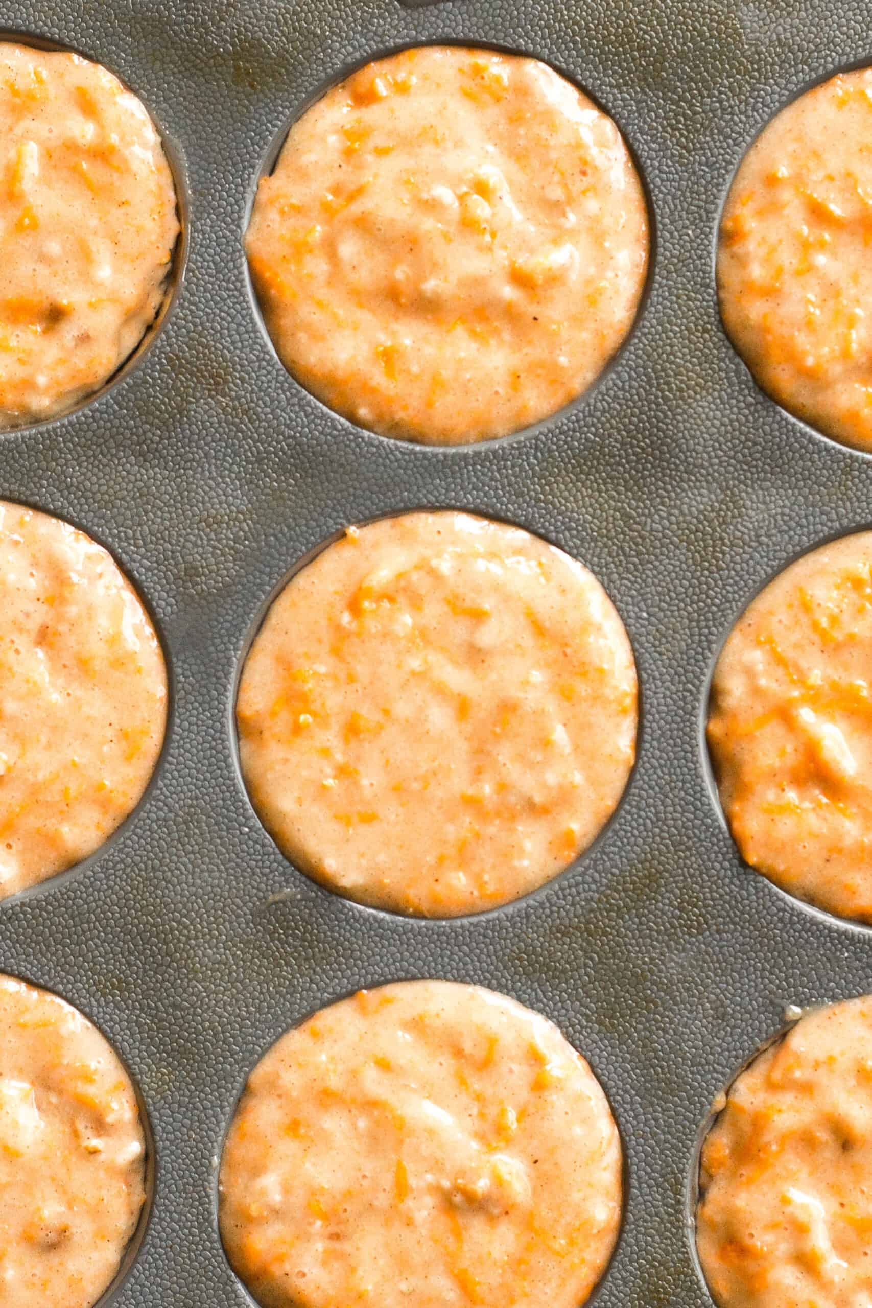 Carrot cake muffin batter in muffin mold.