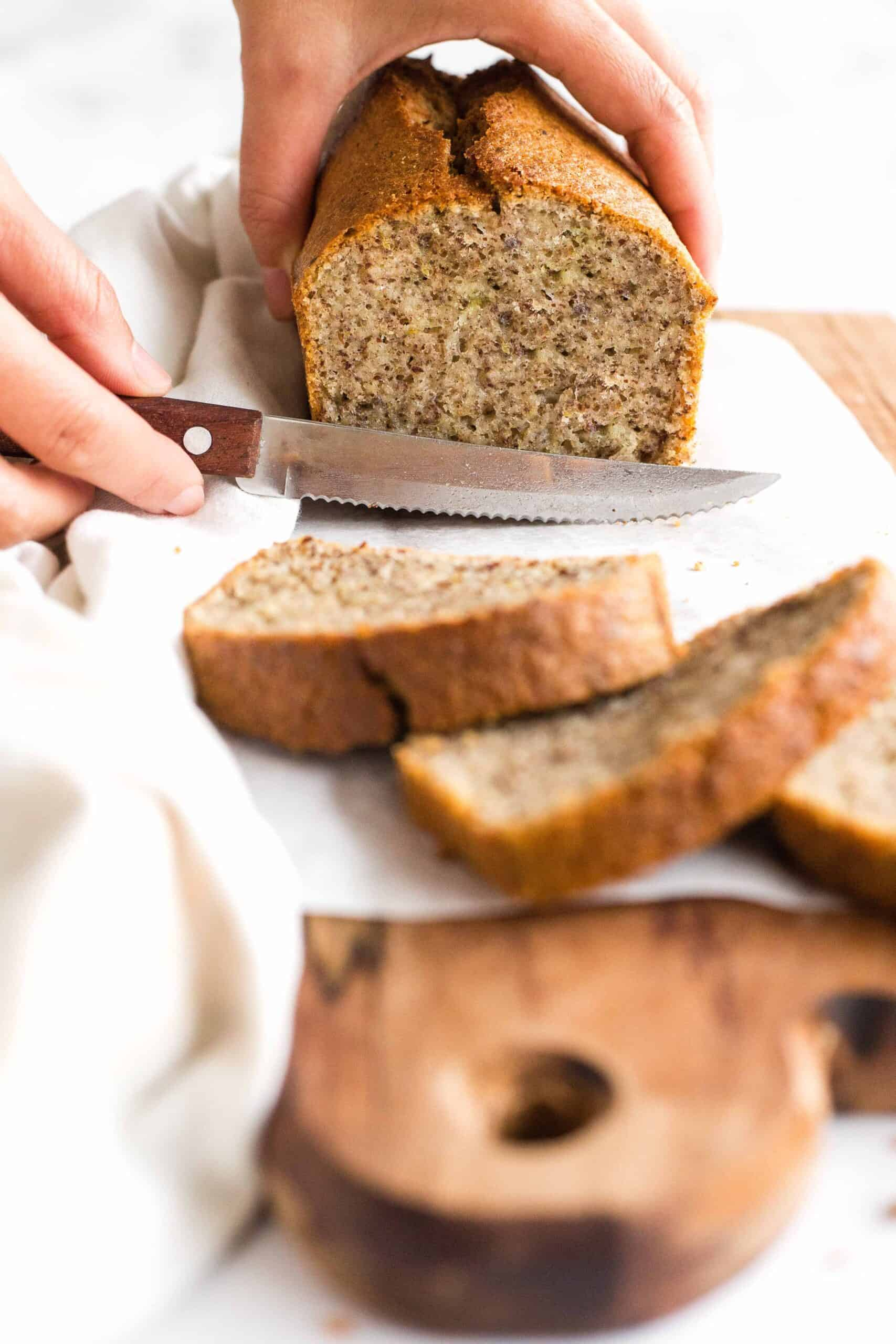 Slicing into a loaf of flaxseed bread on a wooden board.