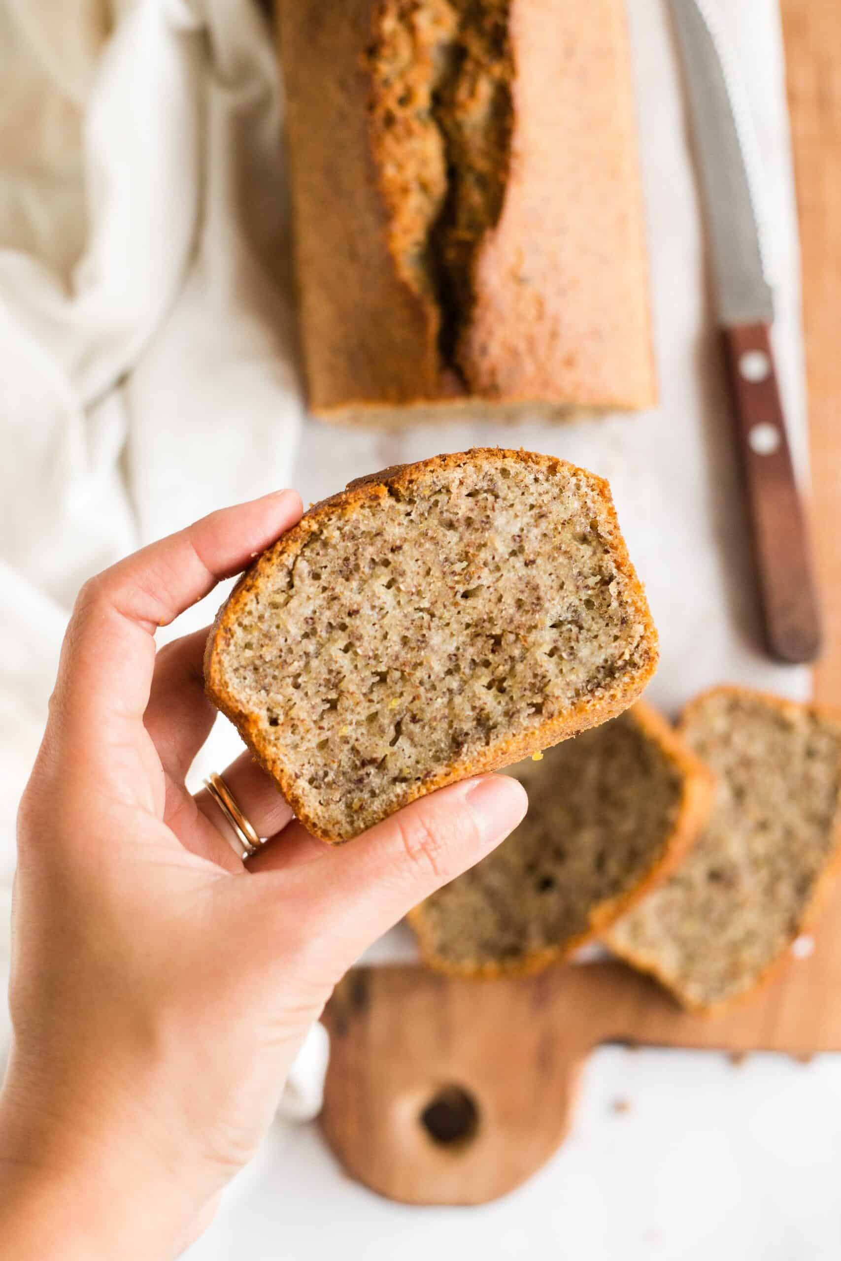 Hand holding up a slice of flaxseed bread from a board.