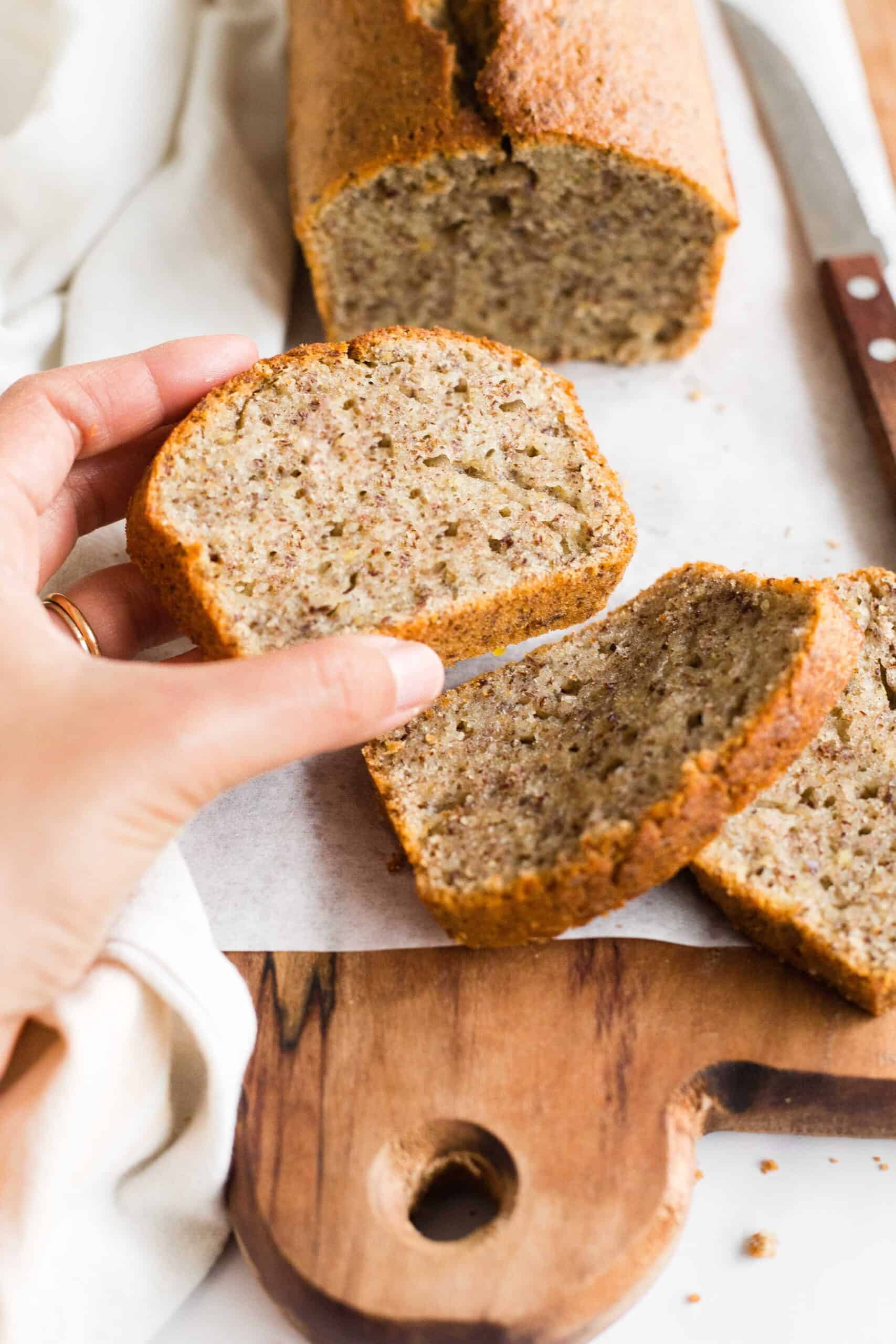 Hand holding a slice of flaxseed bread.