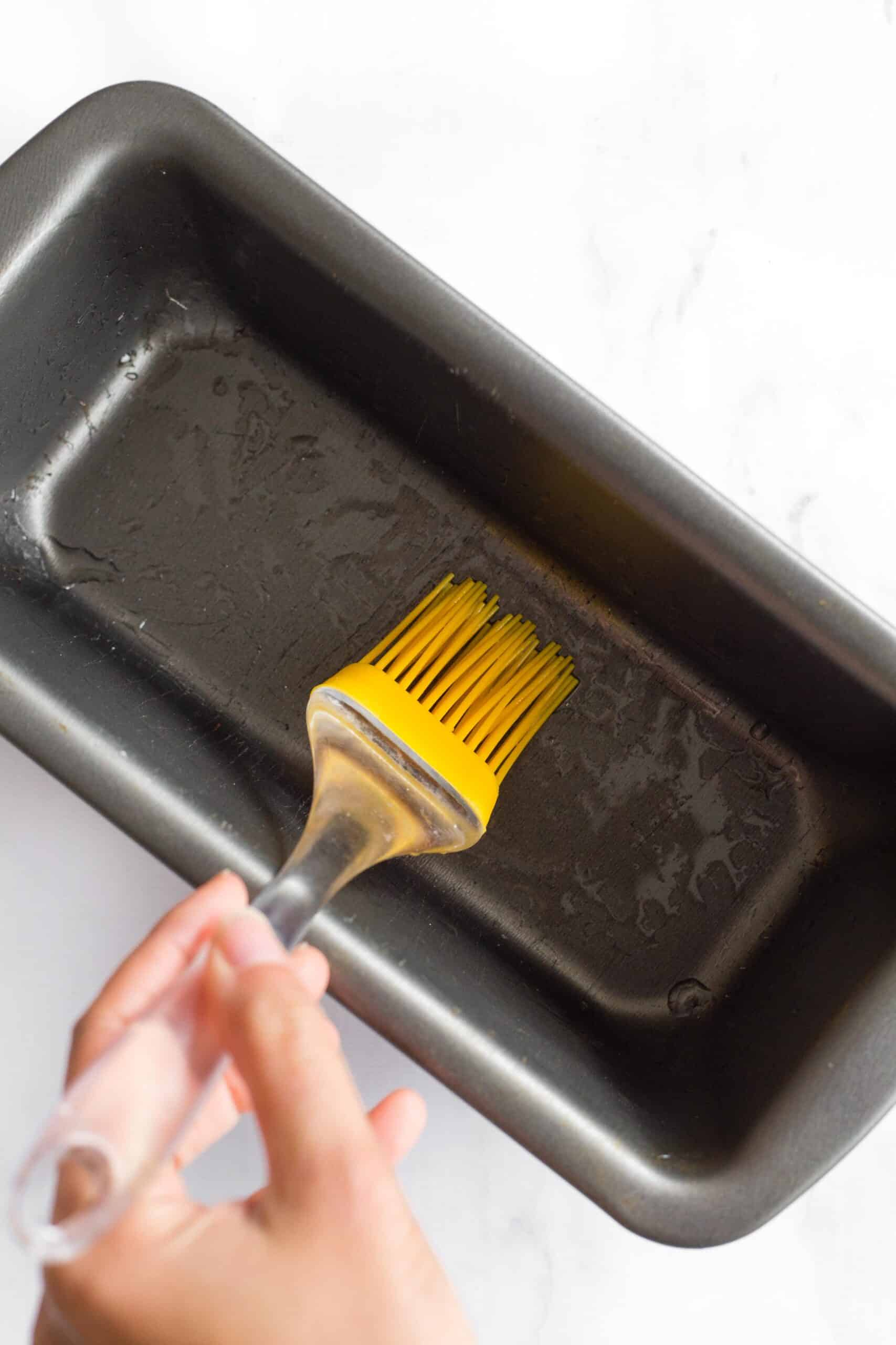 Using a silicon brush to grease a metal loaf pan.