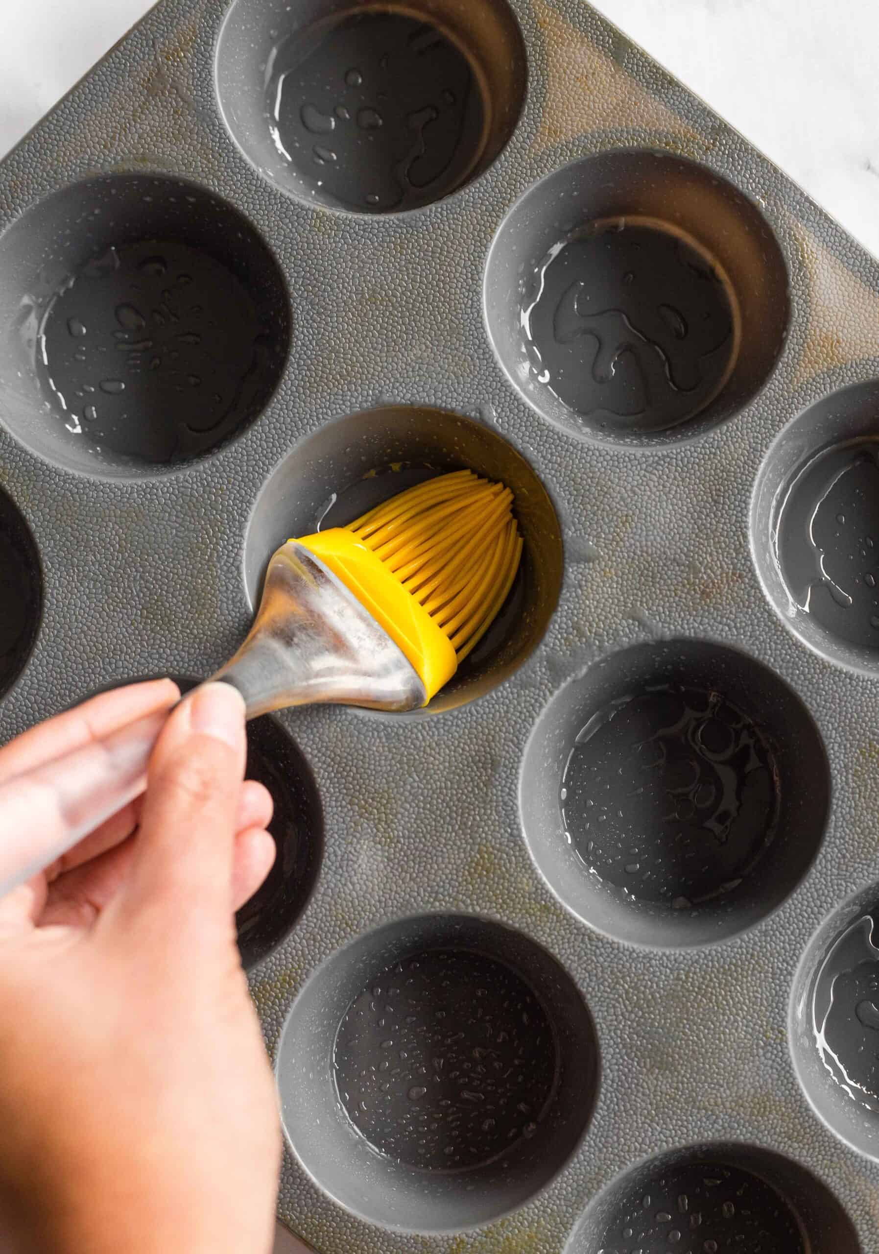 Using a brush to grease a grey silicon muffin mold.
