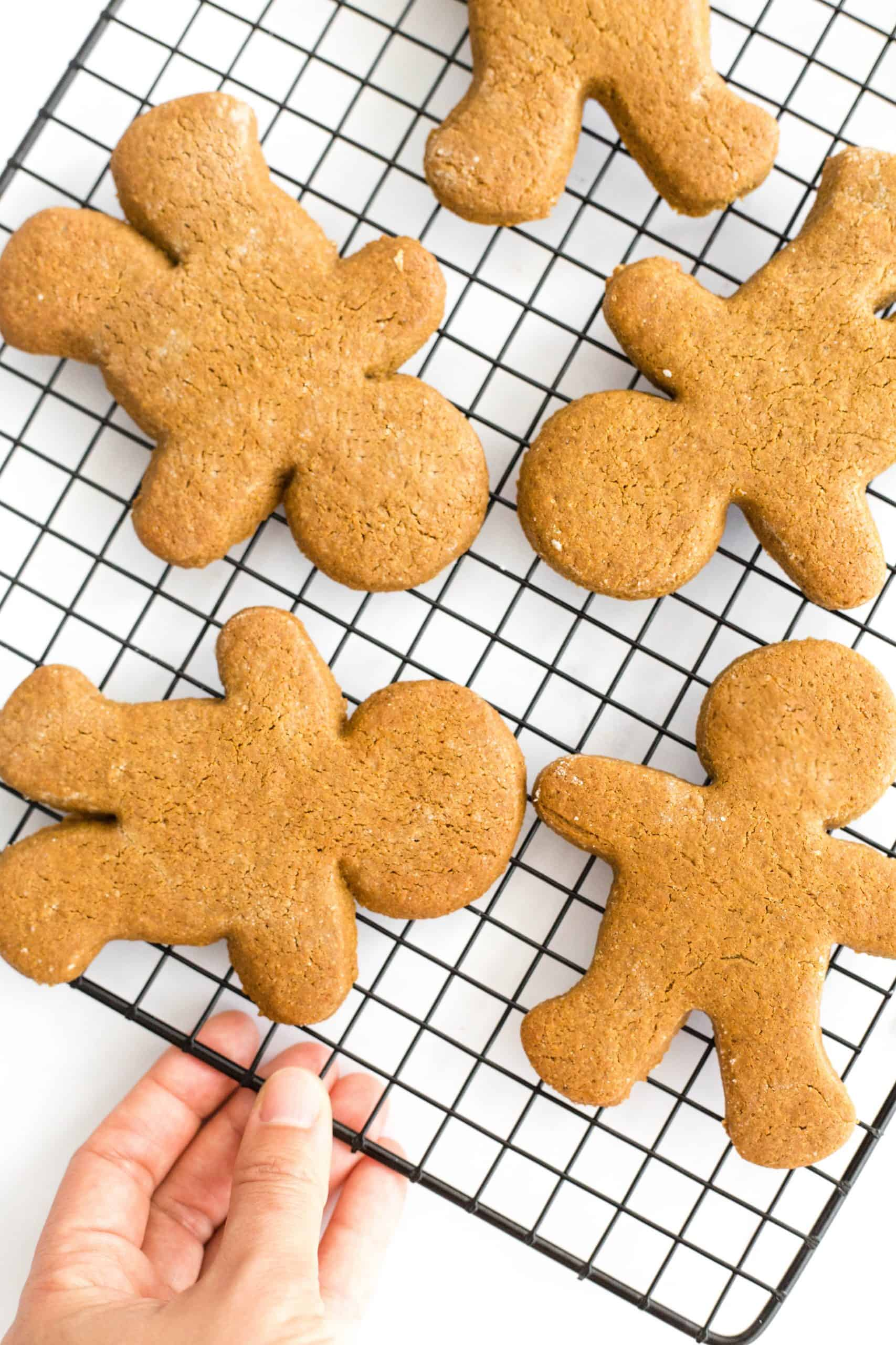 Gingerbread men cooling on a wire rack.