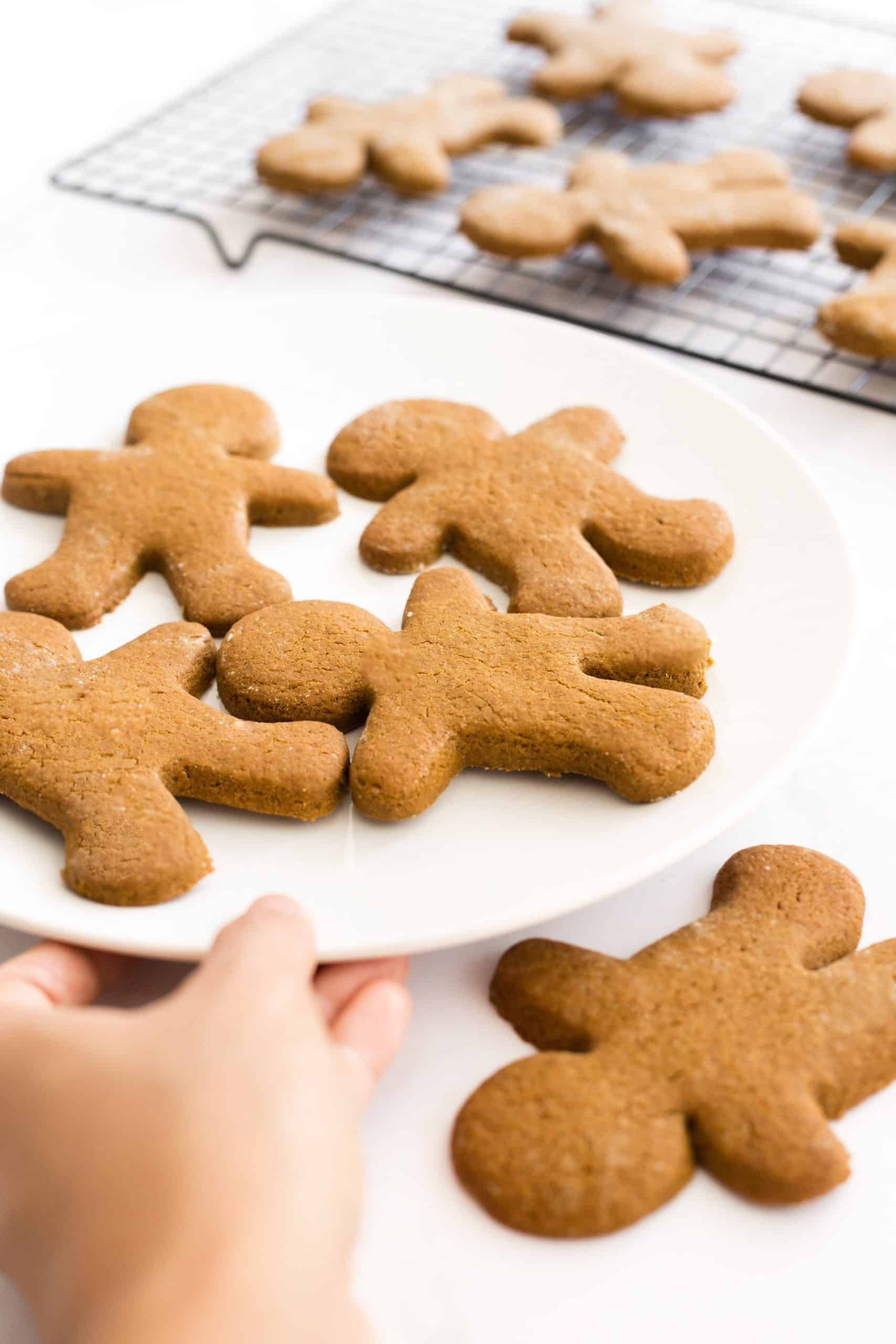 Hand holding a plate of gingerbread men.