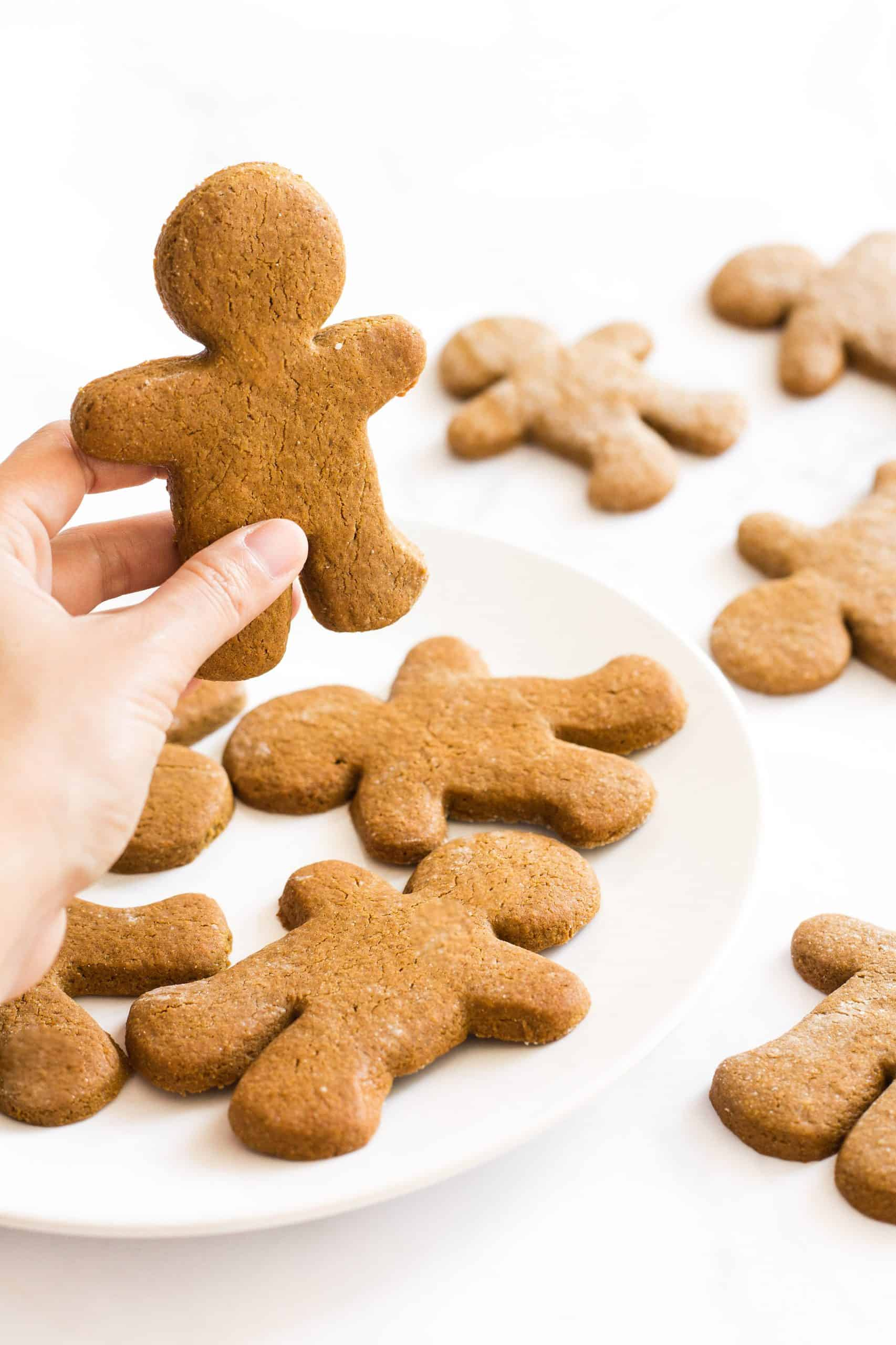 Hand holding up a gingerbread man from a plate of cookies.