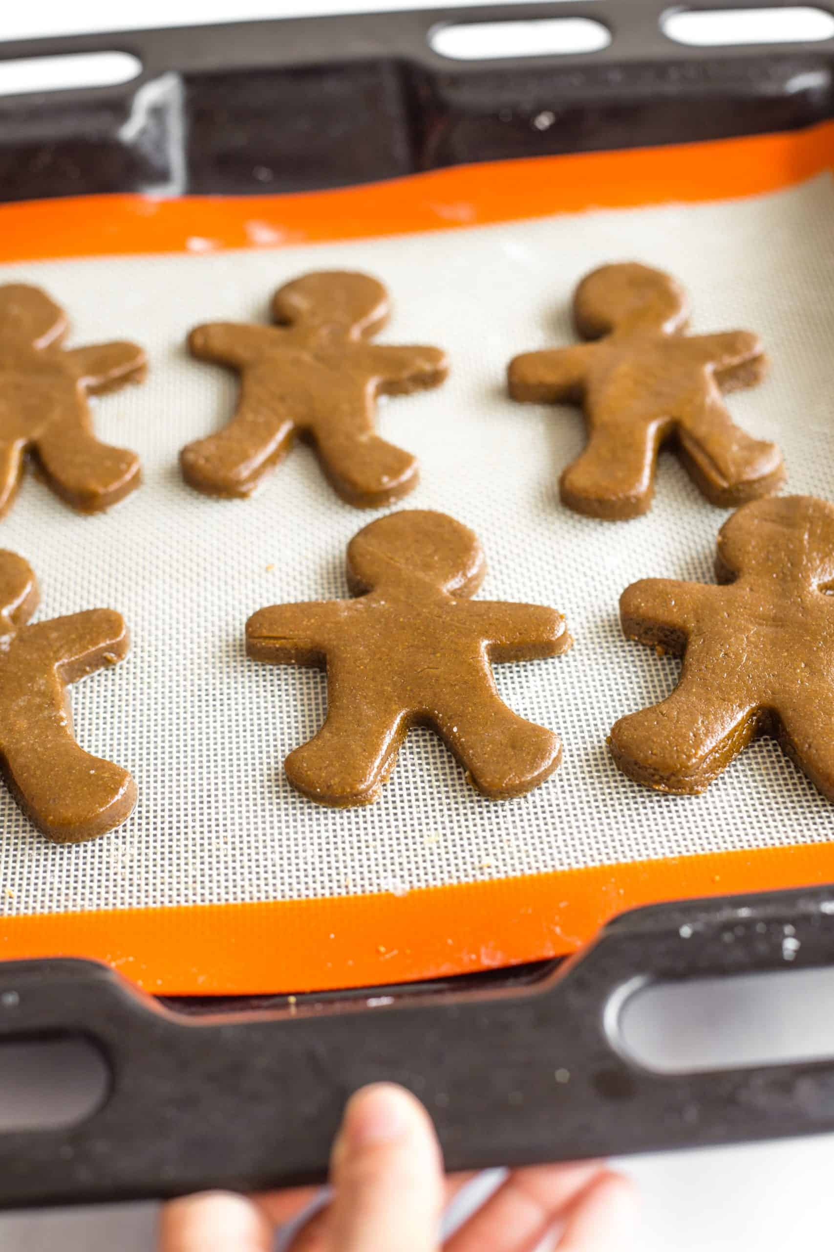 Gingerbread man dough pieces on silpat-lined baking sheet.