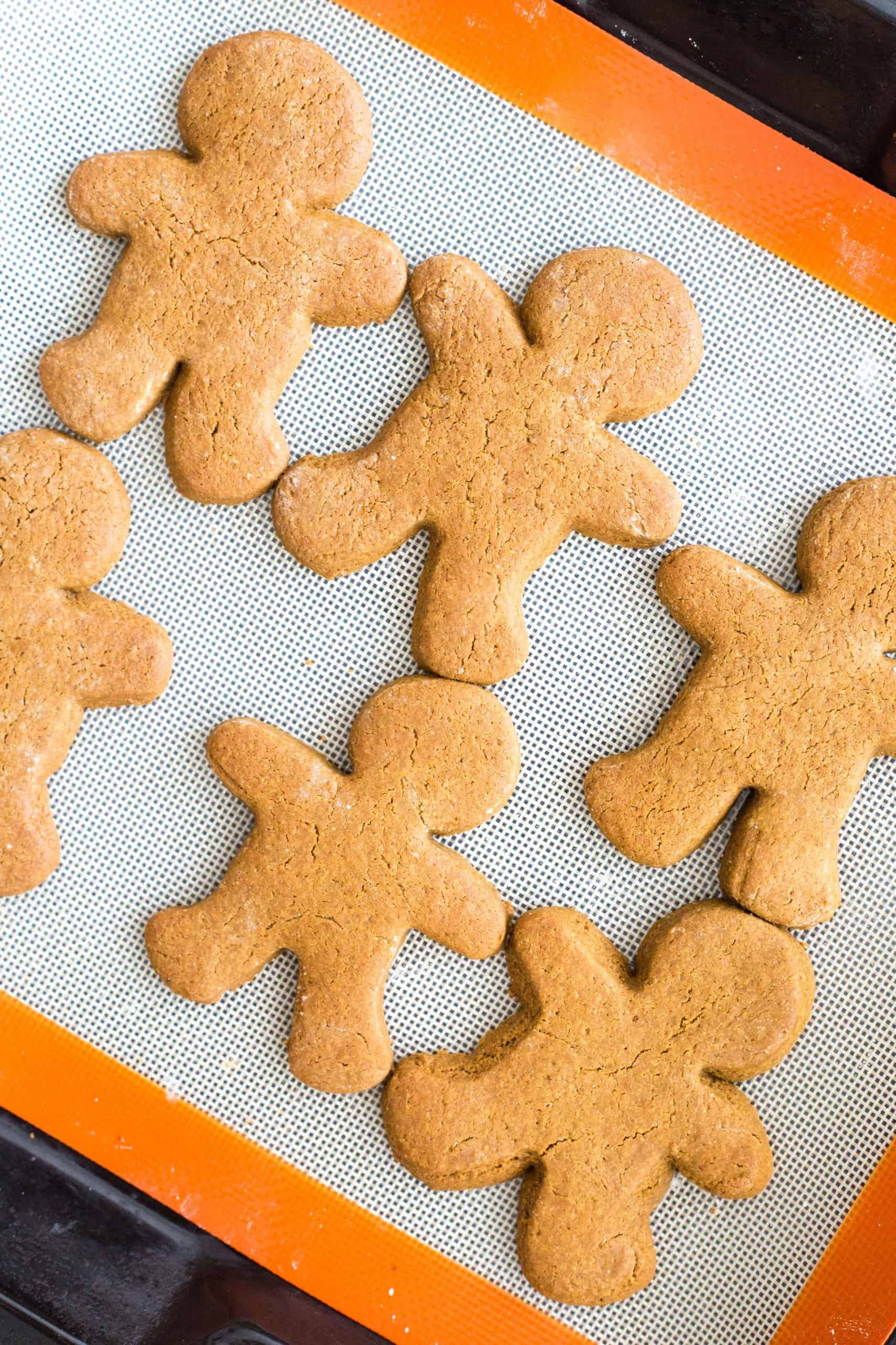 Gingerbread cookies on a silpat-lined baking sheet.