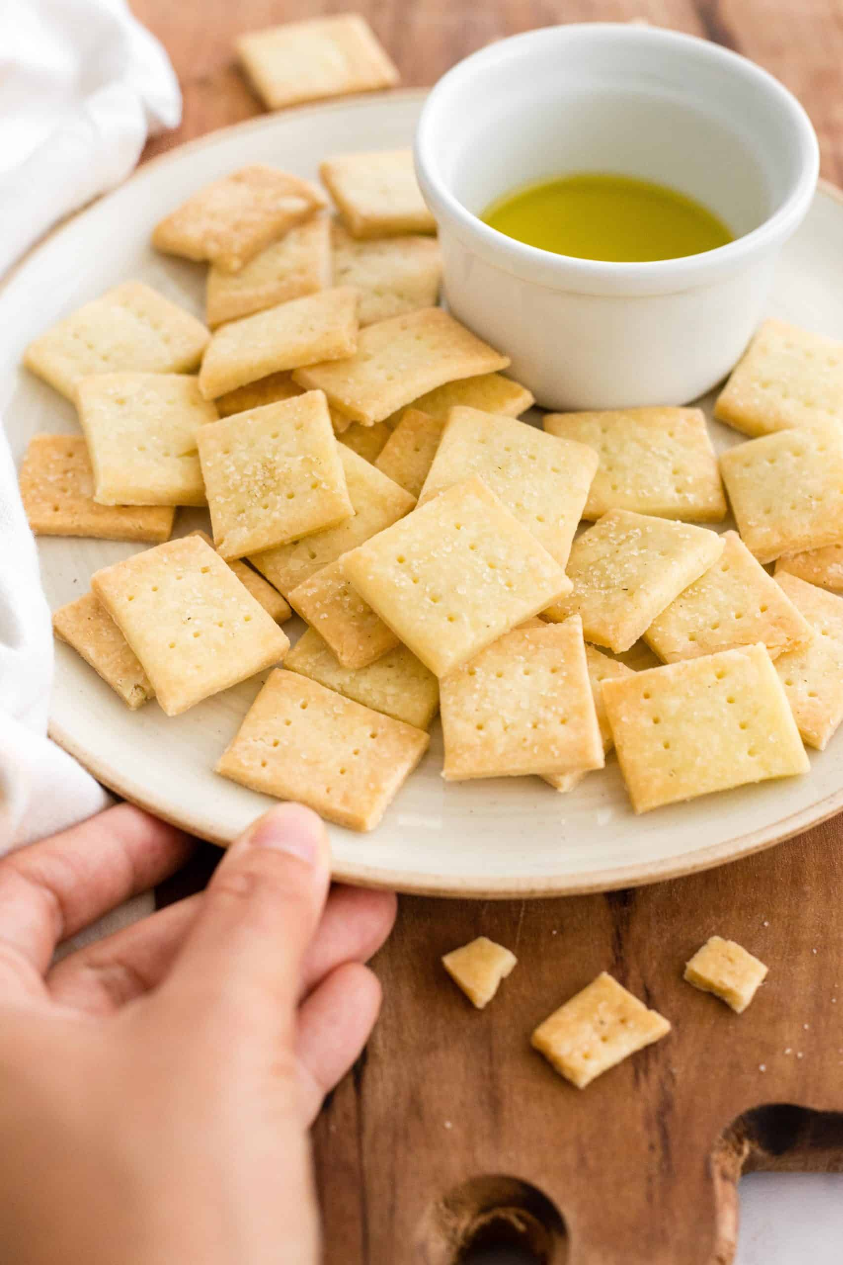 Hand holding a plate of crackers with olive oil.