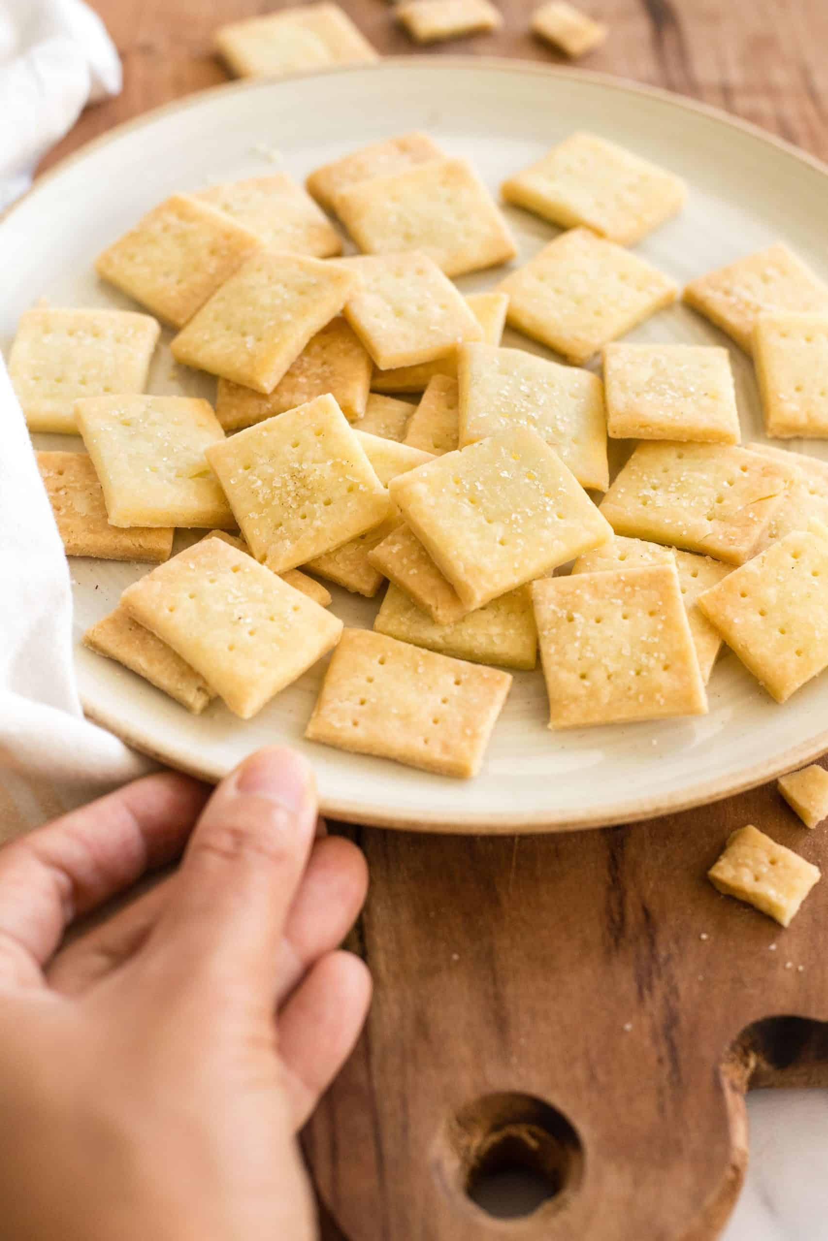 Hand reaching for a plate of crackers.