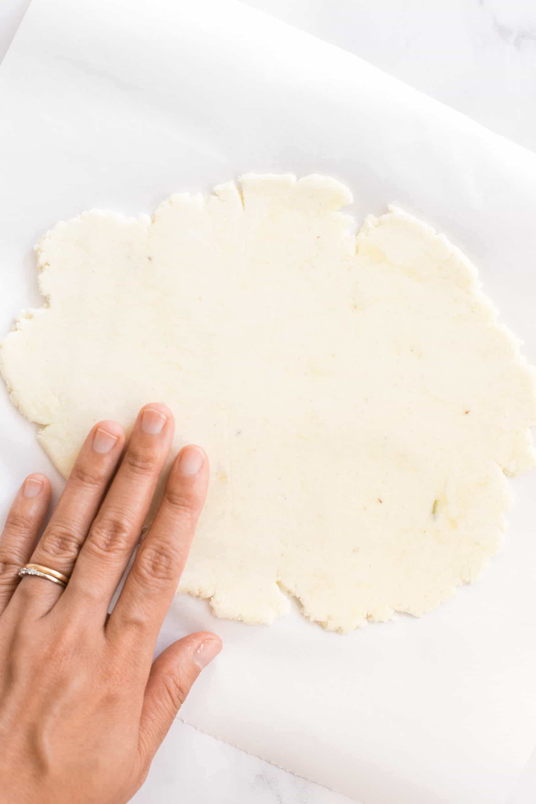 Hand on flattened dough on parchment paper.