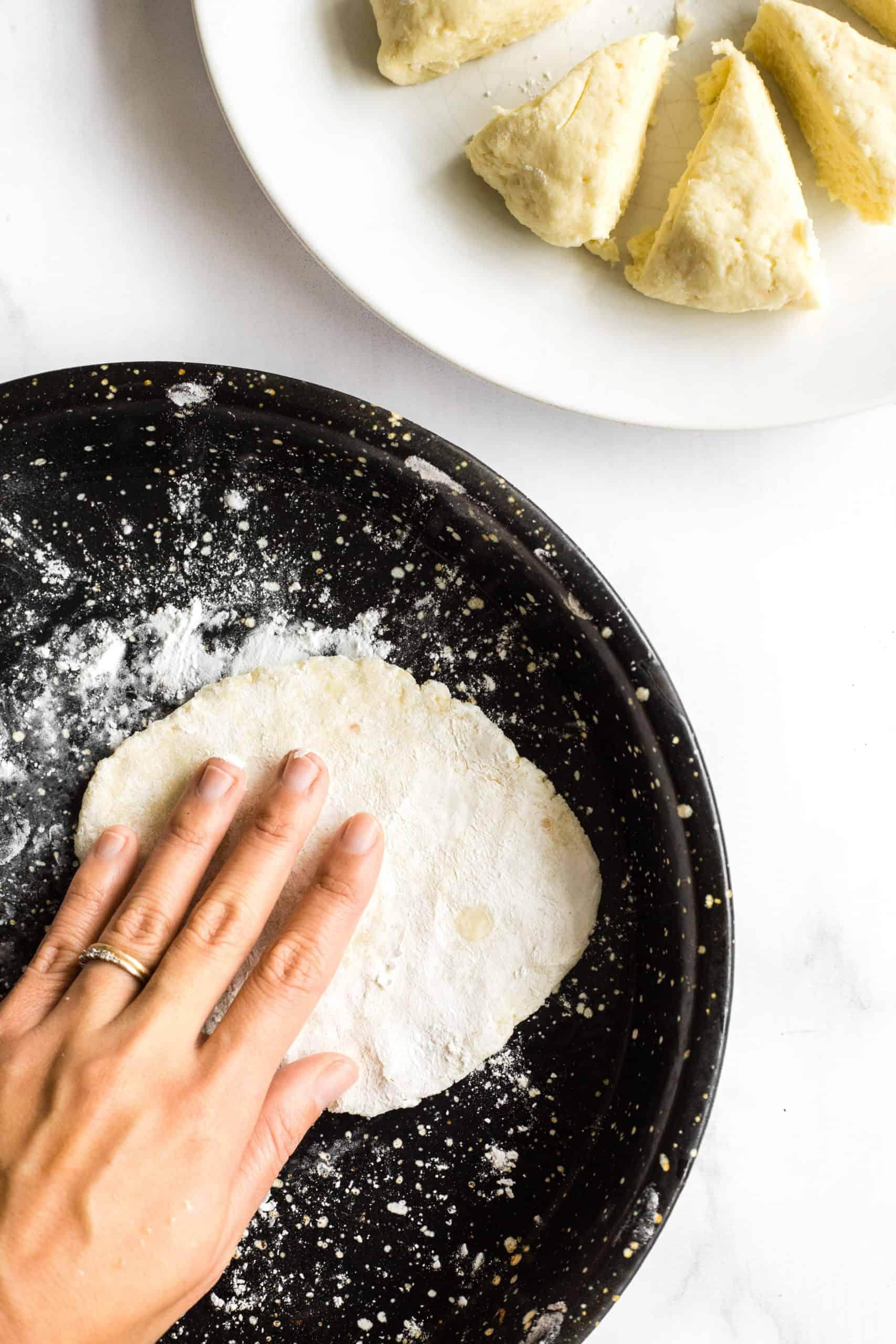 Flattening the gluten-free naan dough with fingers.