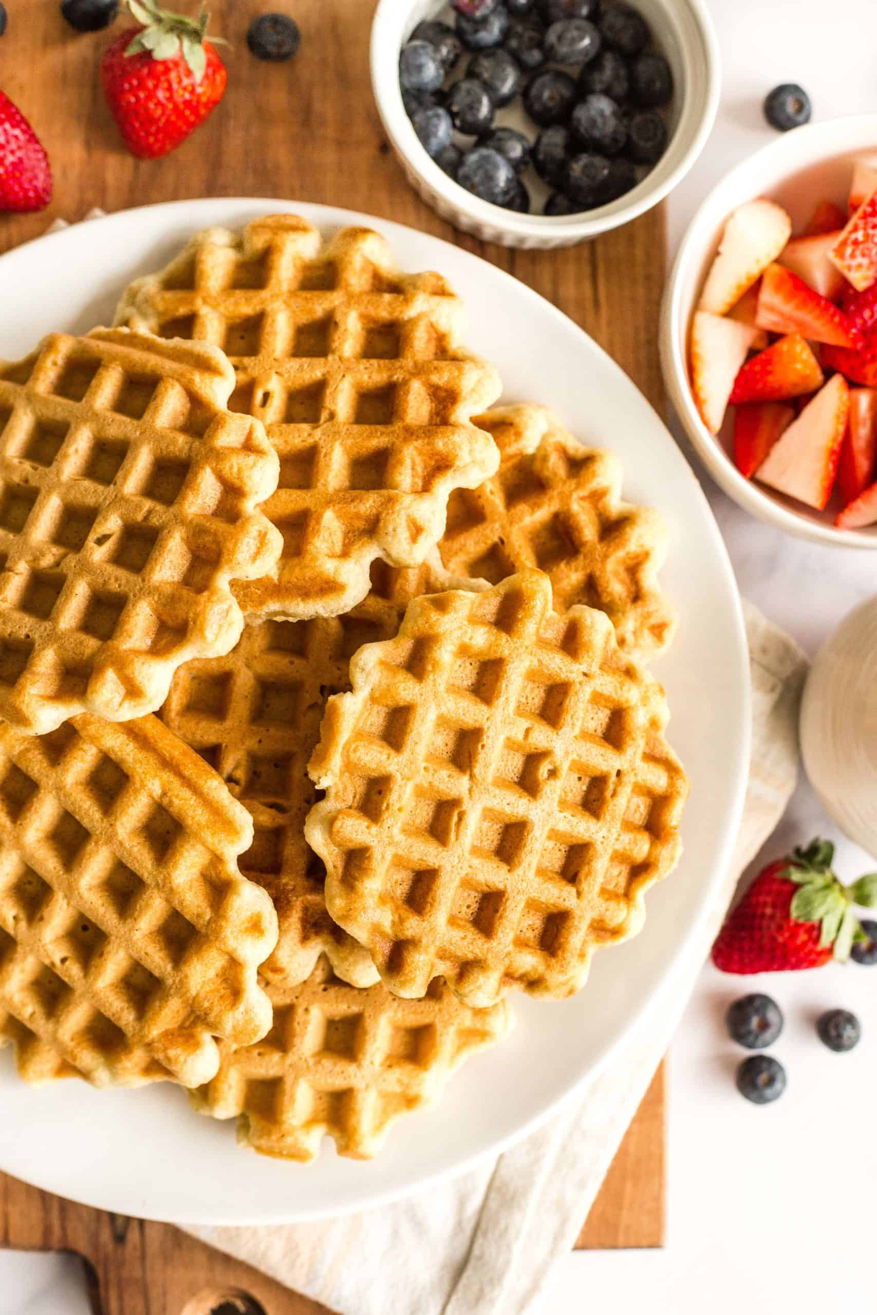Gluten-free waffles on a plate and fresh berries in small bowls on a wooden board.