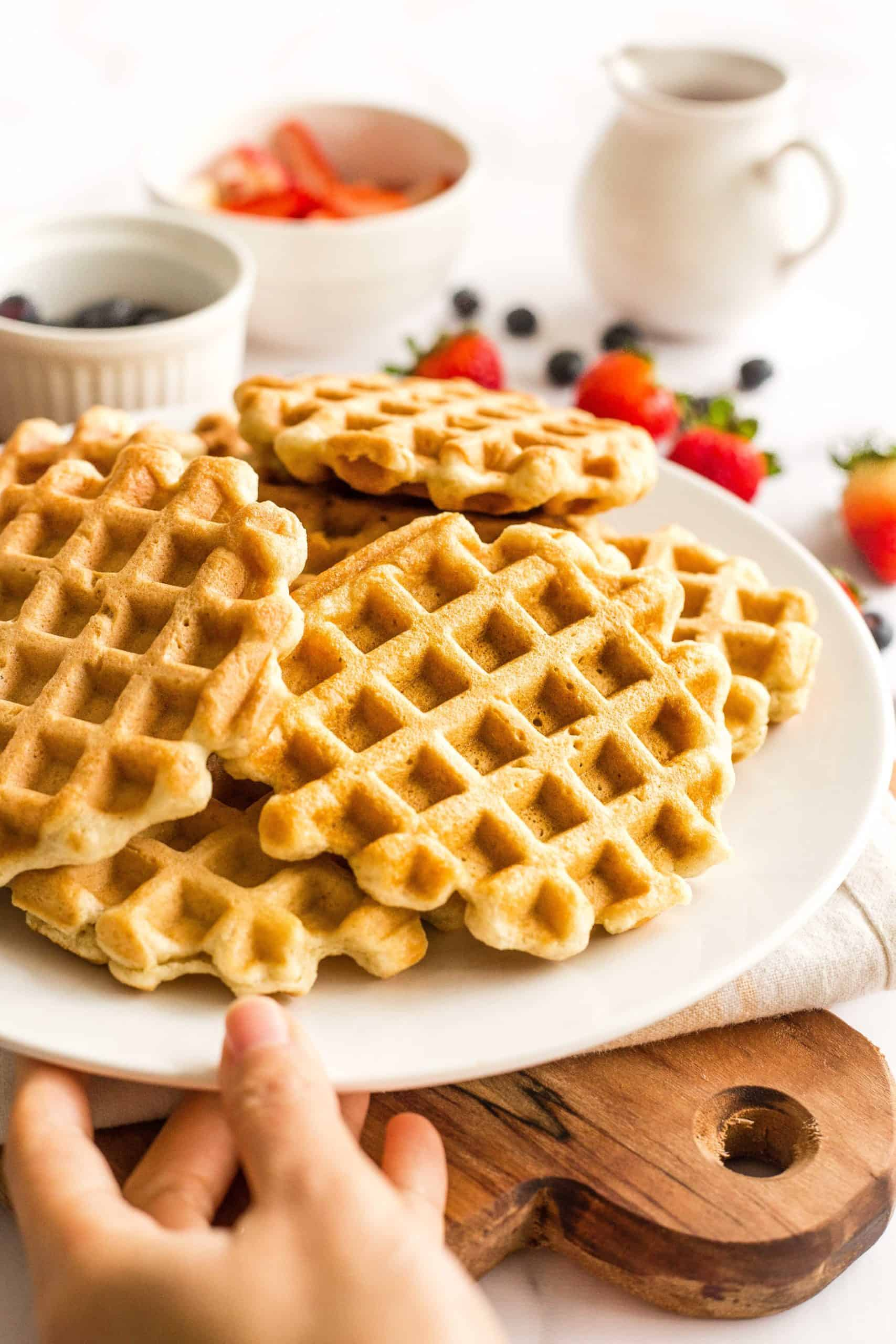 Hand holding a plate full of freshly cooked golden brown gluten-free waffles.