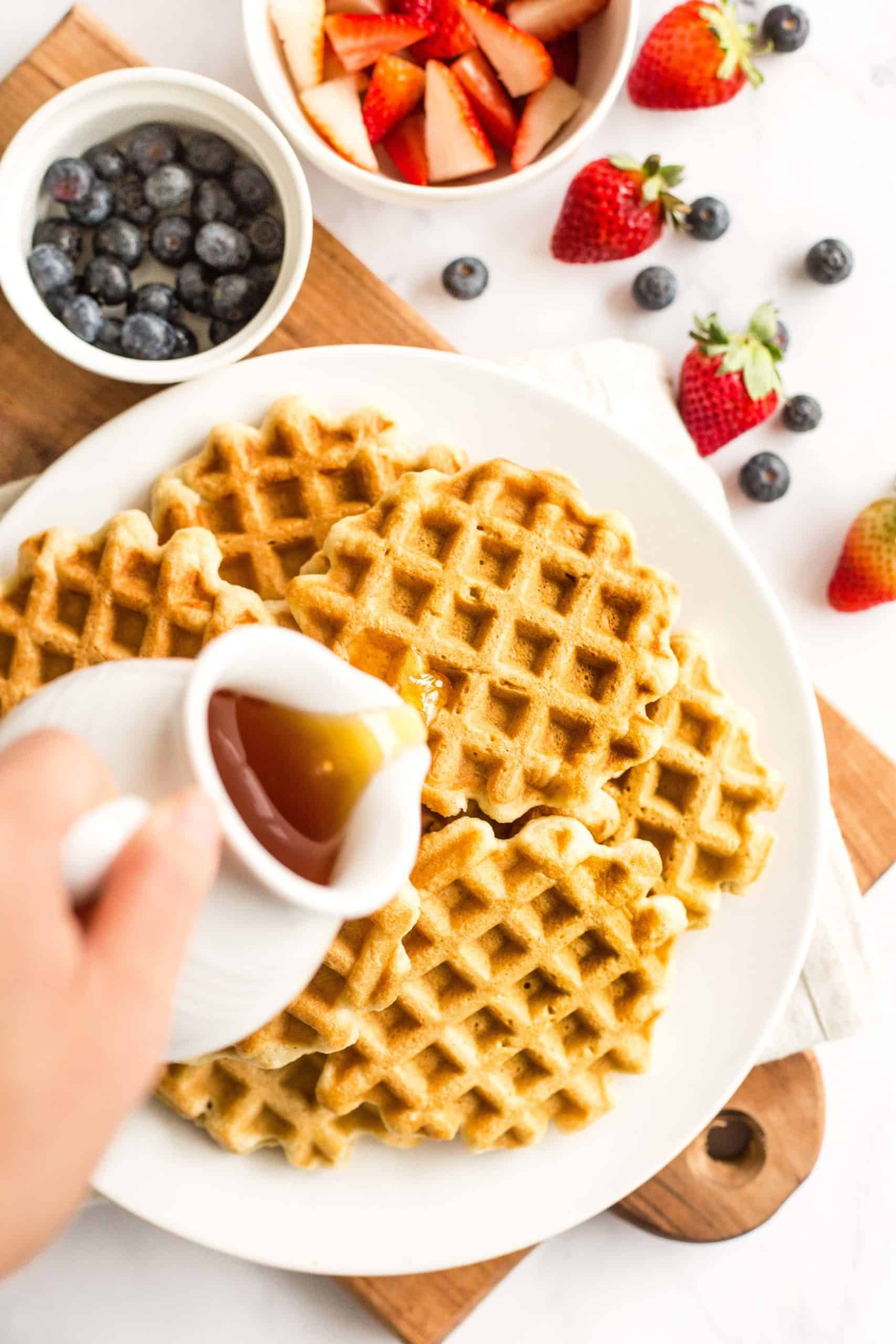Hand pouring maple syrup over a plate of gluten-free waffles and bowls or fresh berries at the side.