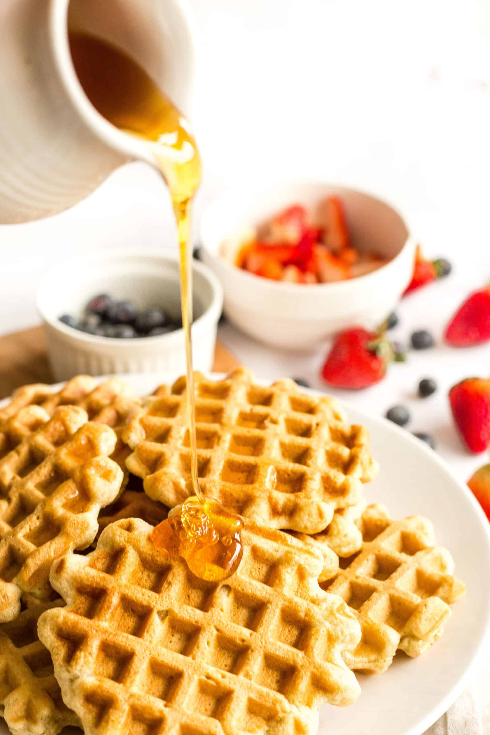 Maple syrup being drizzled over a big plate of waffles.