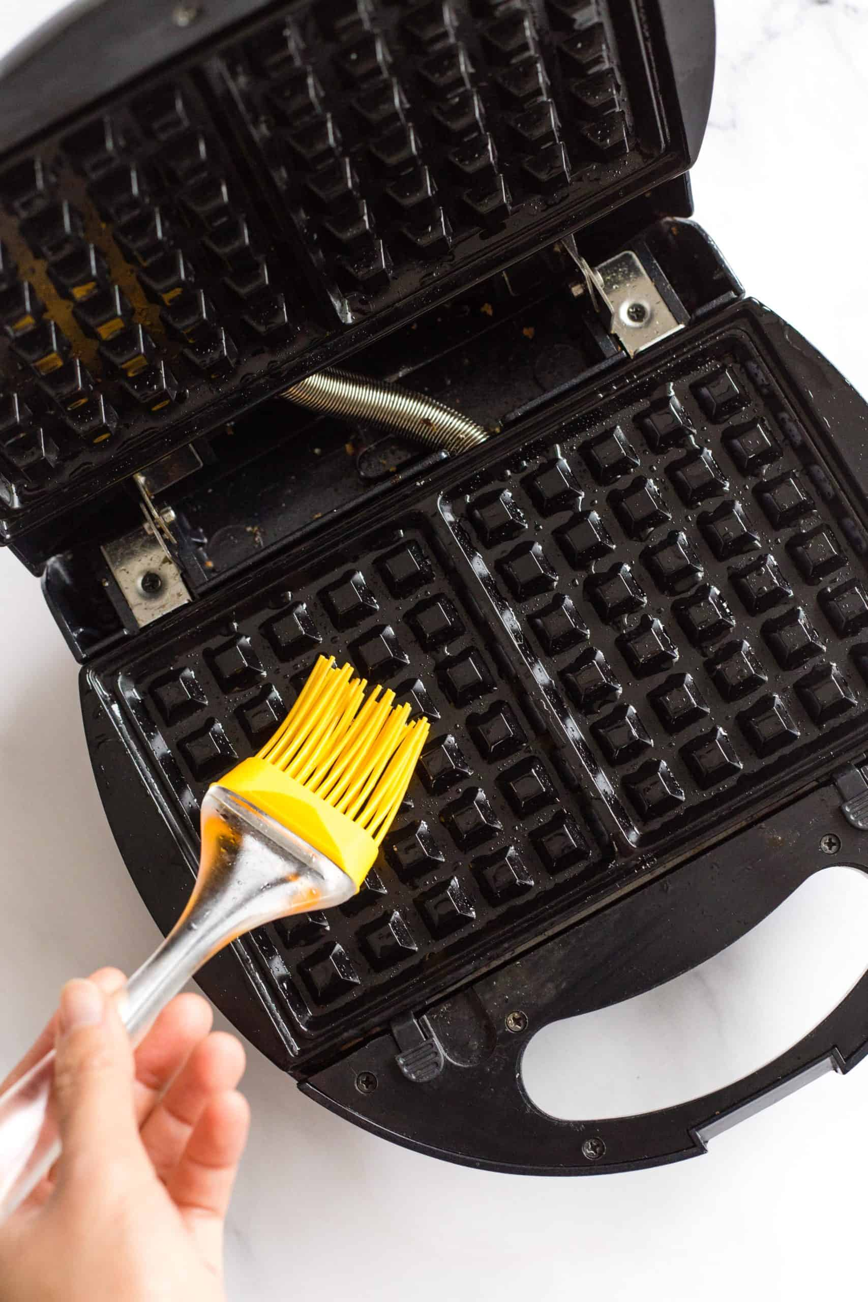Using a silicon brush to brush the waffle iron with vegetable oil.