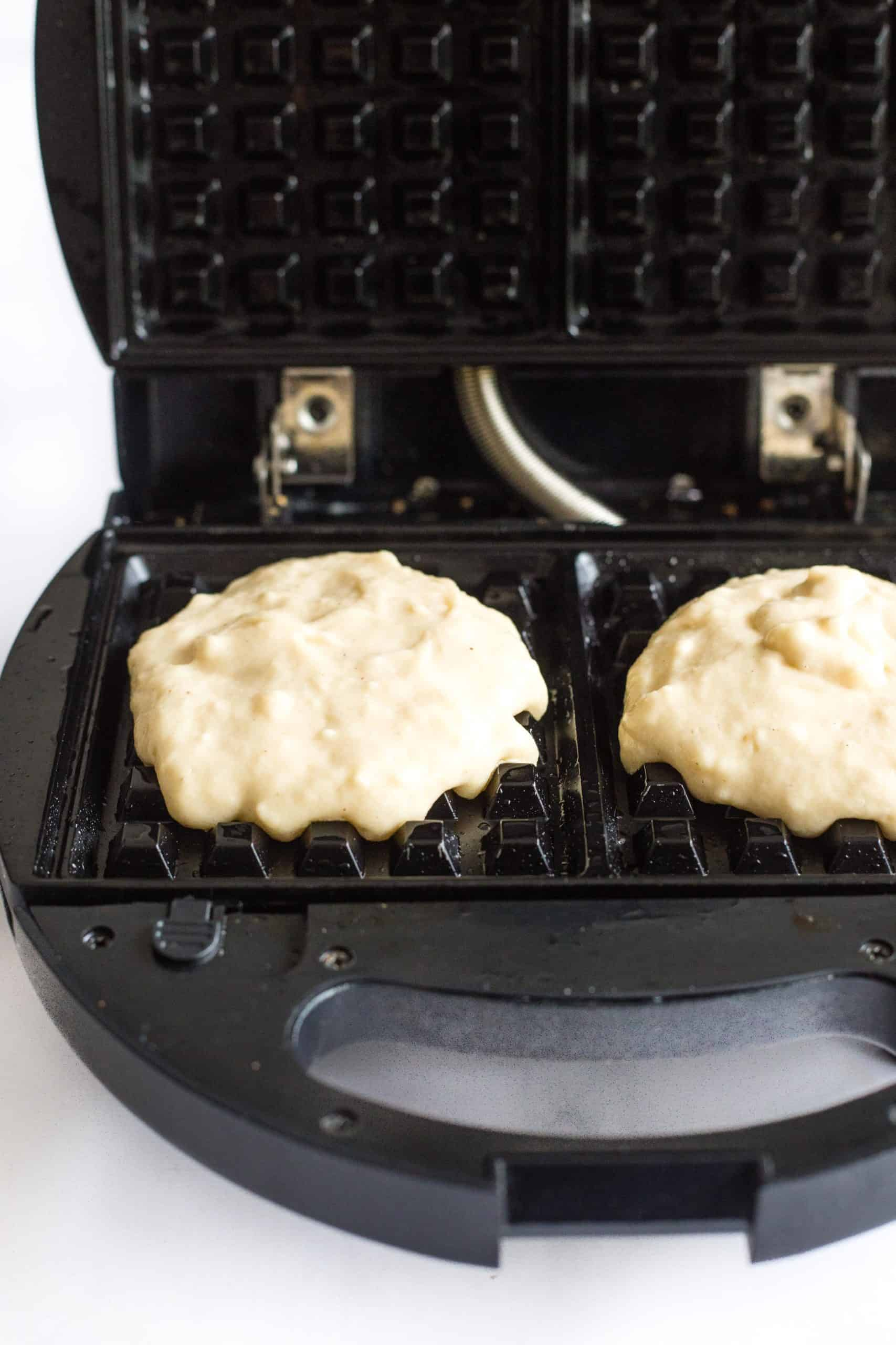Gluten-free waffle batter poured onto the waffle iron and ready to be cooked.