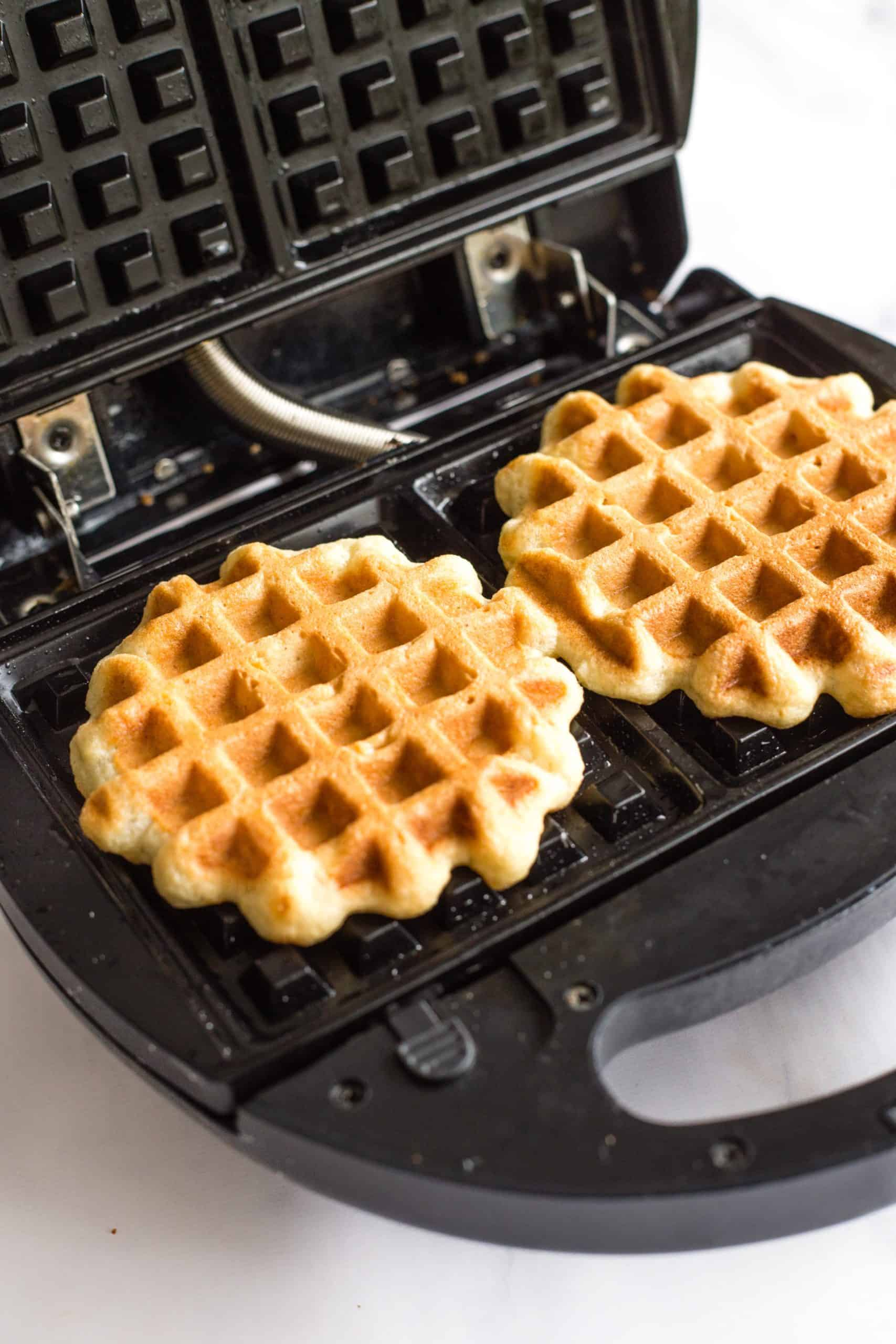 Freshly cooked golden brown crispy waffles in the waffle iron.