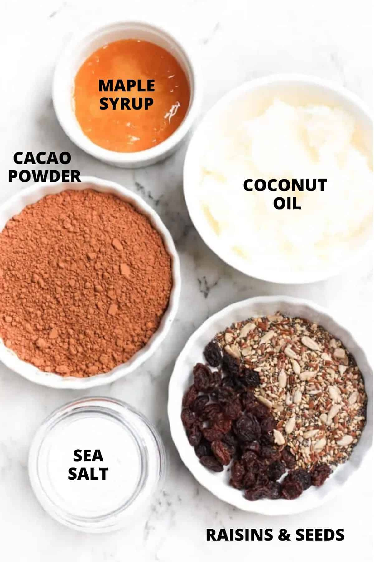 Labeled ingredients for homemade chocolate on marble board.